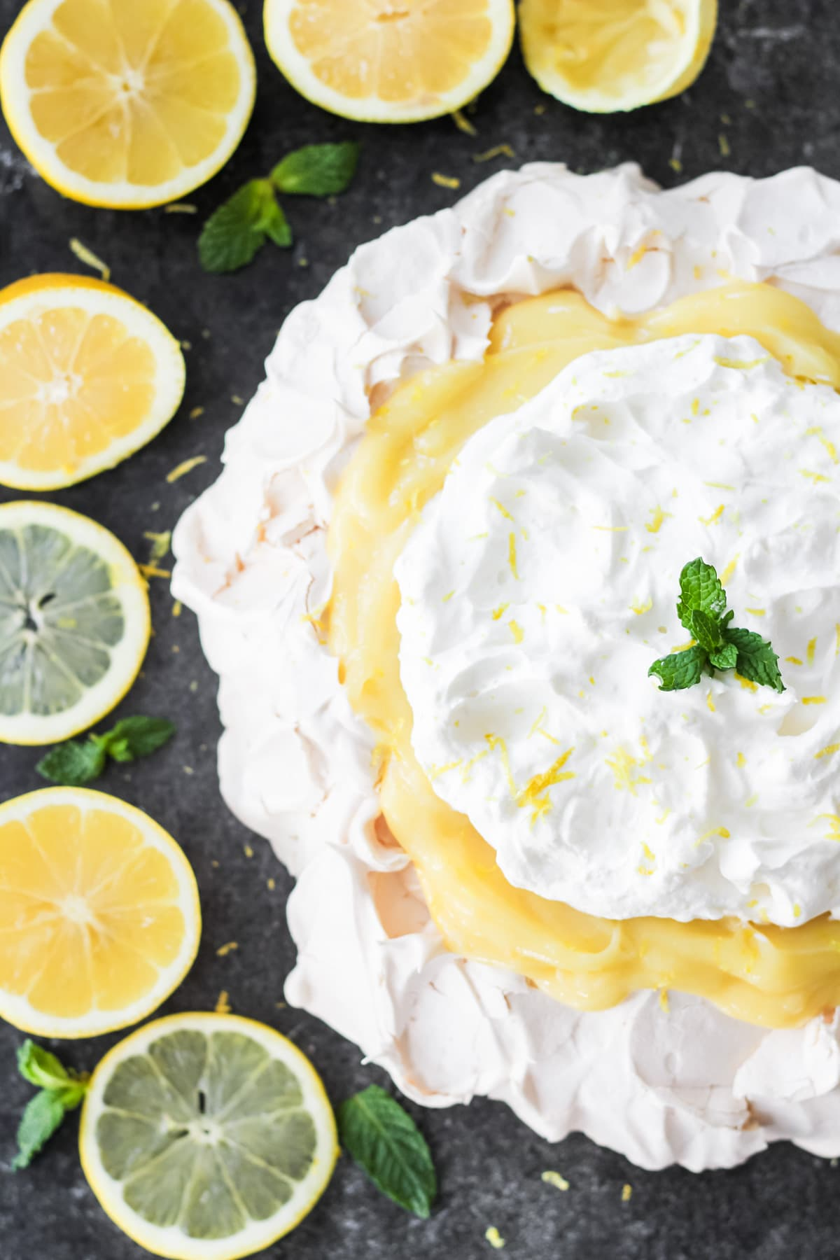 a top down view of half of a lemon pavlova with lemon curd and whipped cream. in the background are sliced lemons and sprigs of mint