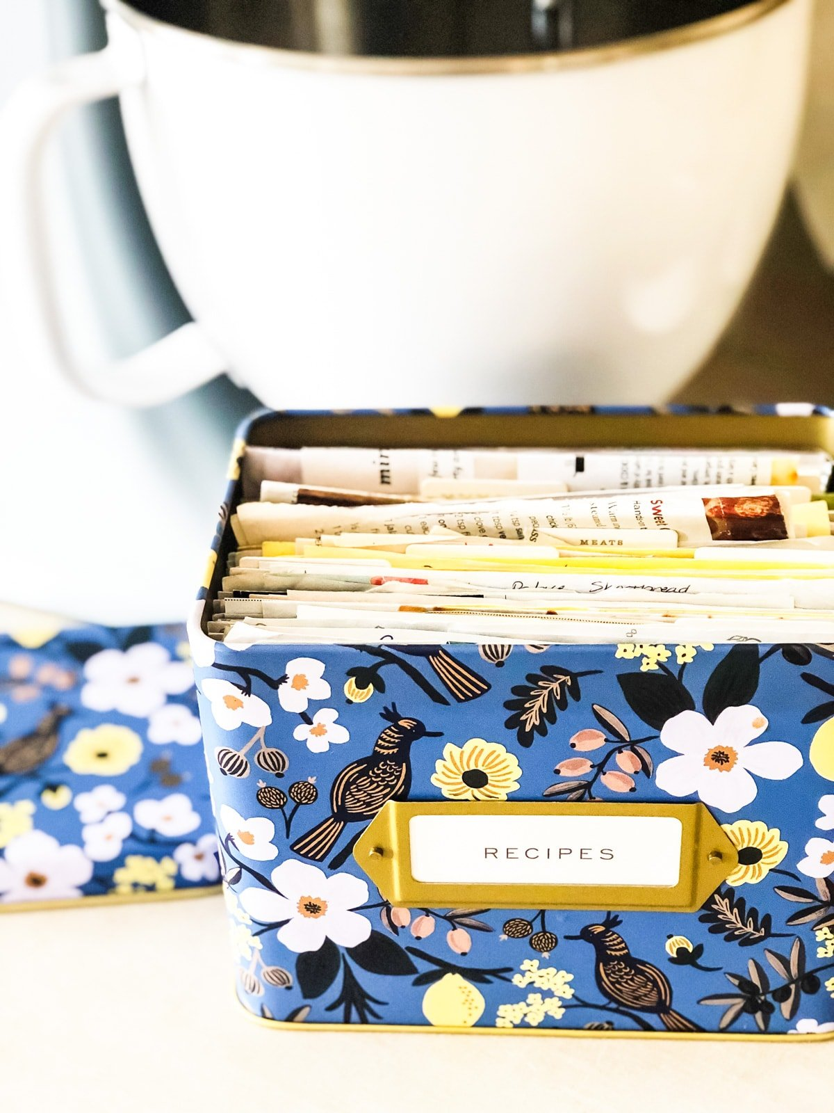 a flowery recipe box sitting on a kitchen counter in front of a kitchen mixer