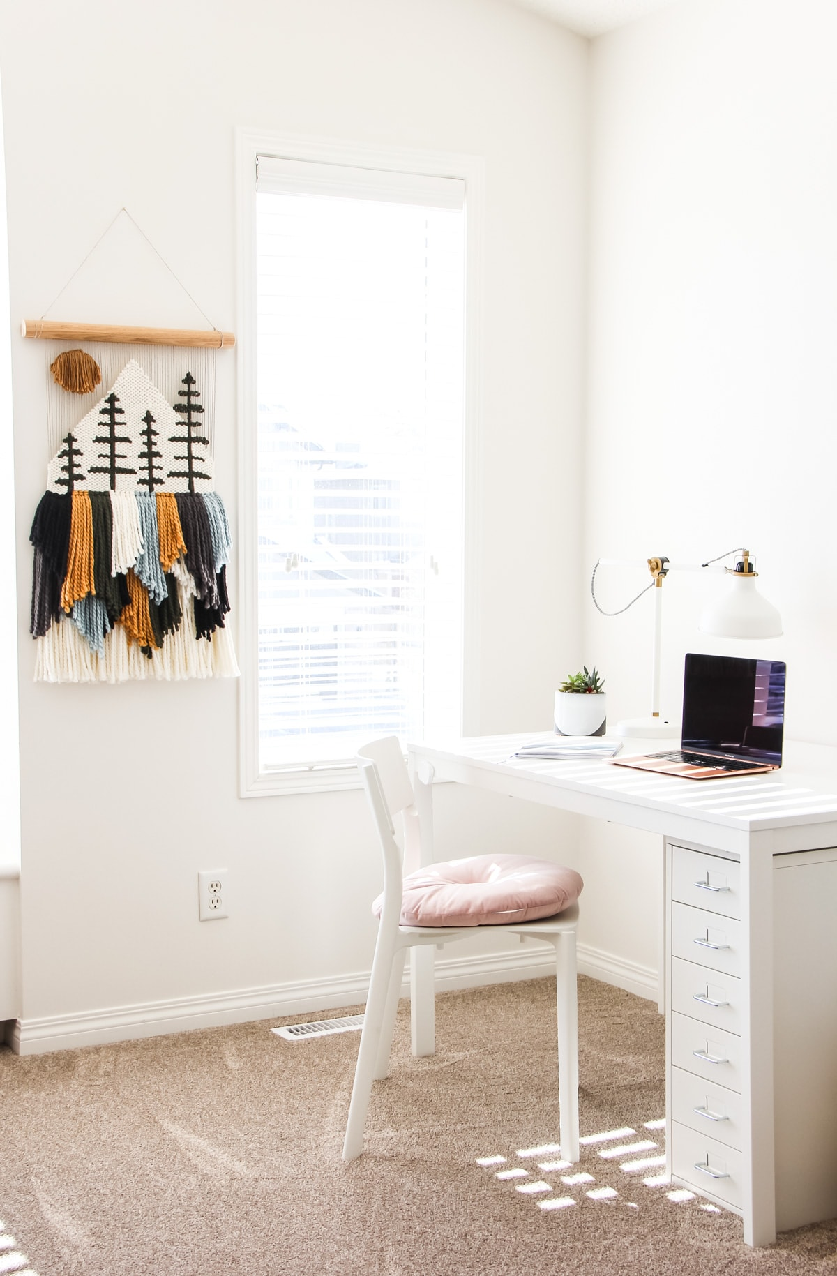 a white desk and chair sitting in a sunny office space. on the wall is a yarn wall hanging