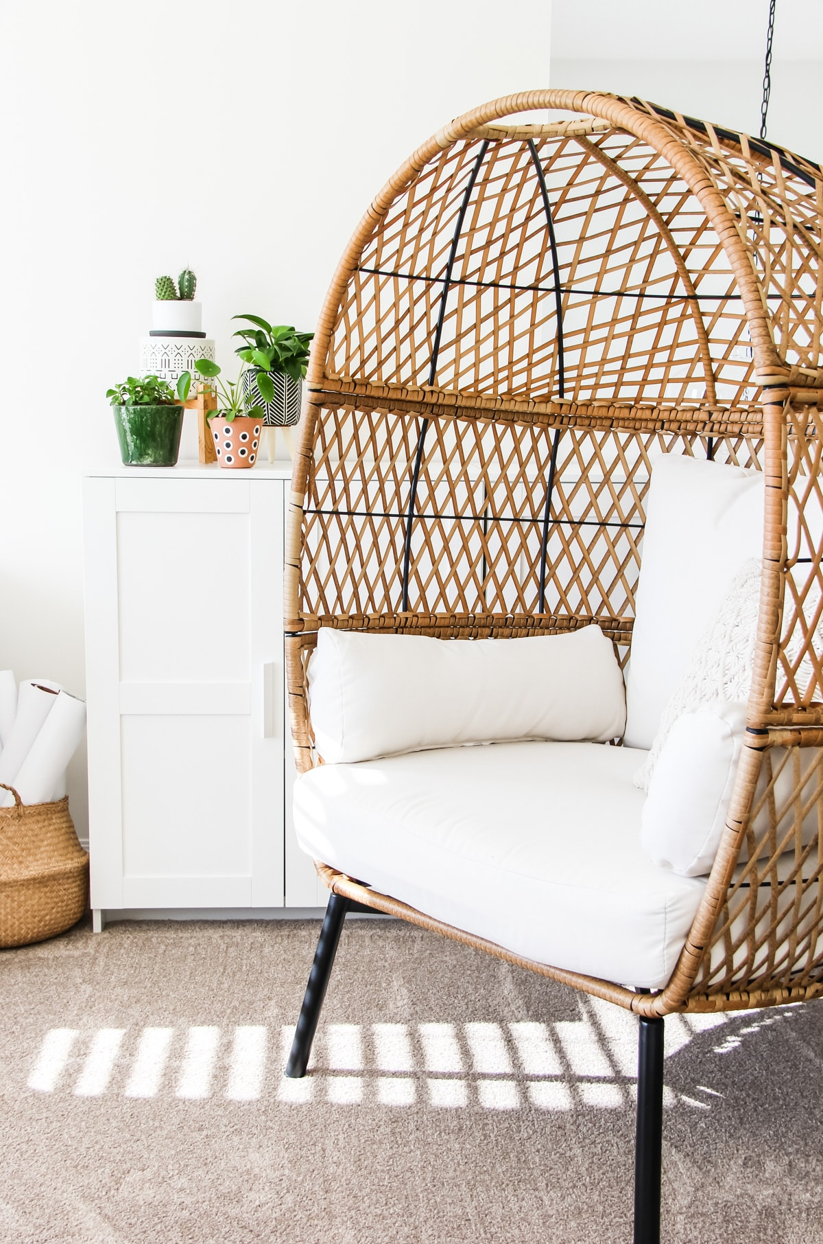 a brown wicker egg chair. in the background is a white shelf with a small collection of plants