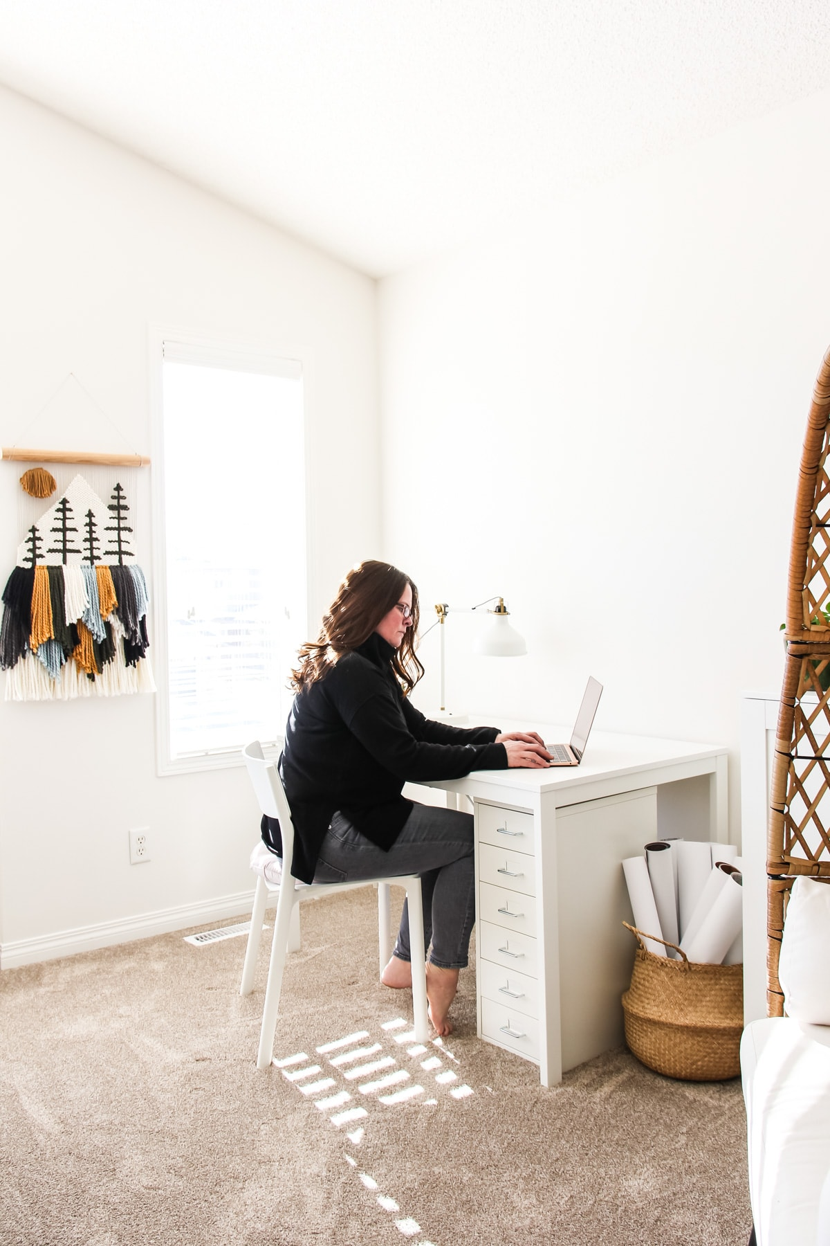 a small office space with a lady dressed in black working at a white desk. on the wall in the background is a yarn wall hanging.