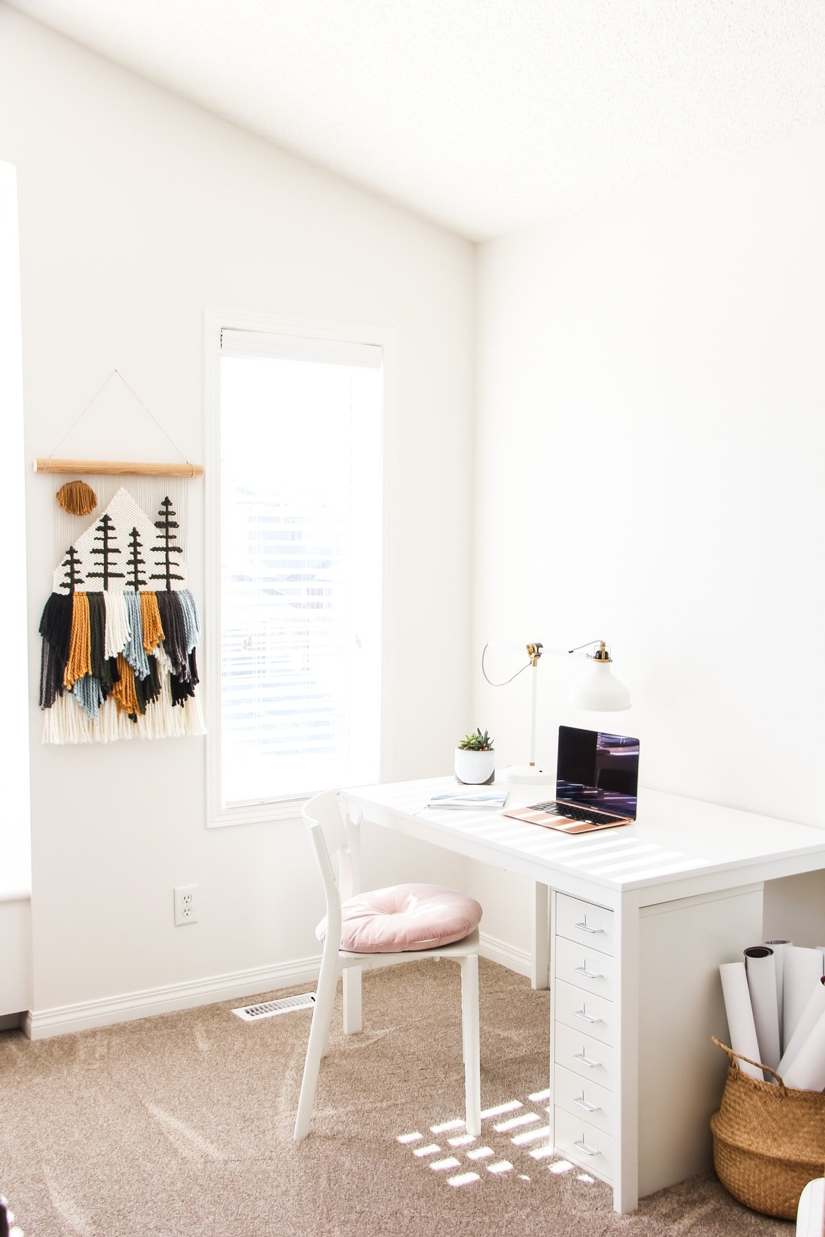 a small office space with a white desk, and white chair with a pink cushion. on the wall is a yarn wall hanging.