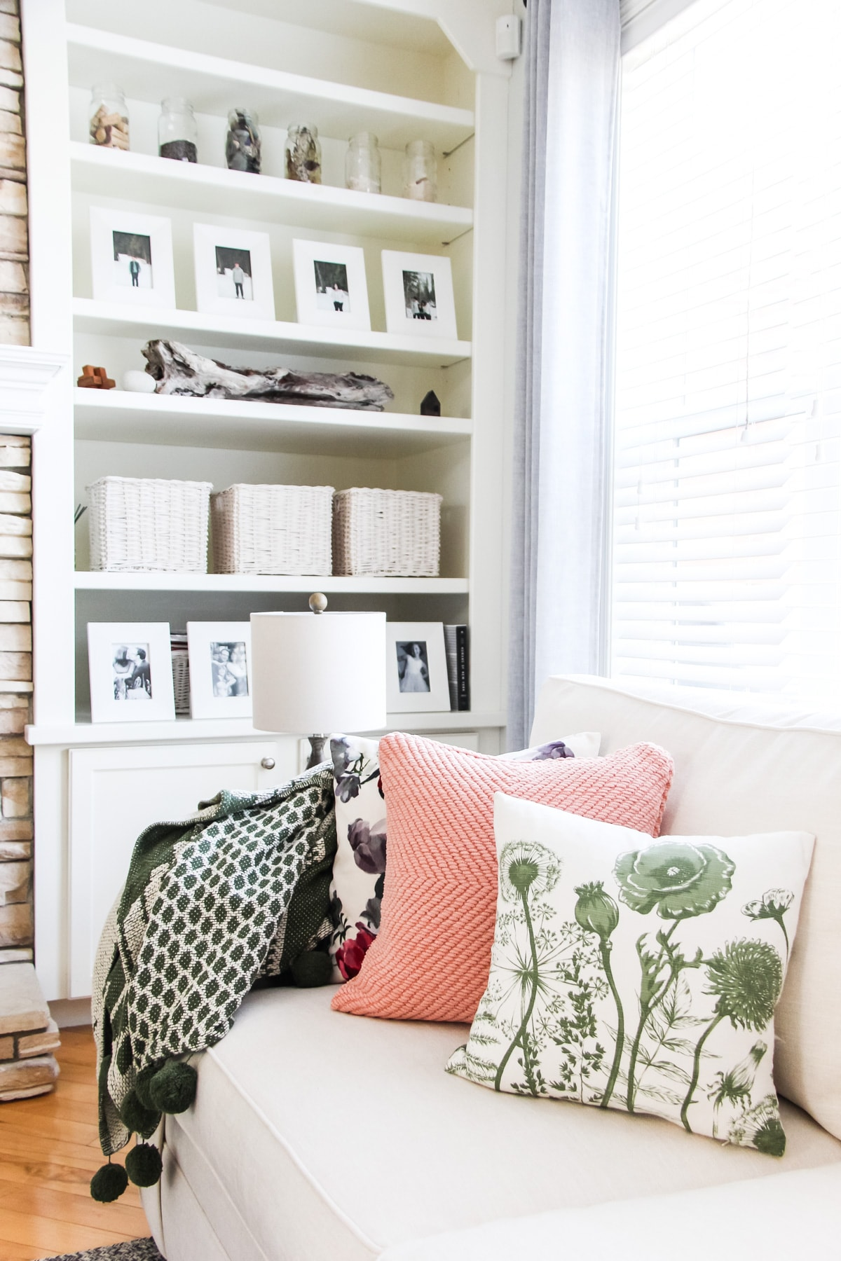a picture of a white sectional couch in a living room with throw pillows and blankets. in the background is a stone fireplace and white bookcase shelving
