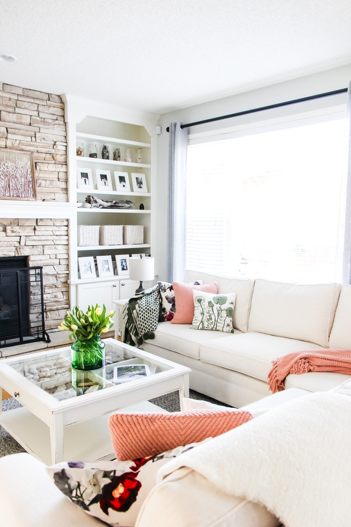a picture of a white sectional couch in a living room with throw pillows and blankets. on a coffee table is a bouquet of tulips. in the background is a stone fireplace and white bookcase shelving