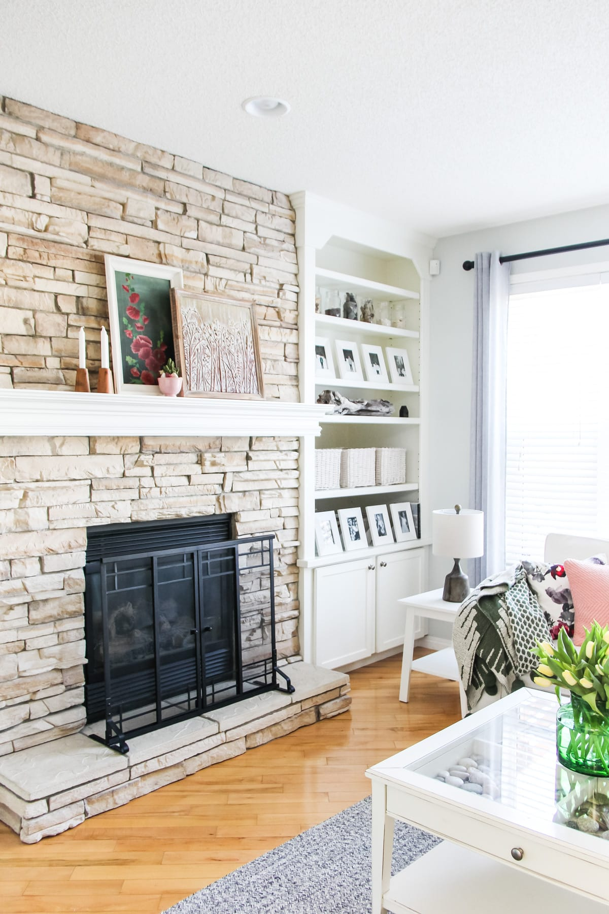 a sandstone fireplace with a white mantel decorated with two pieces of art, candles and a small cactus
