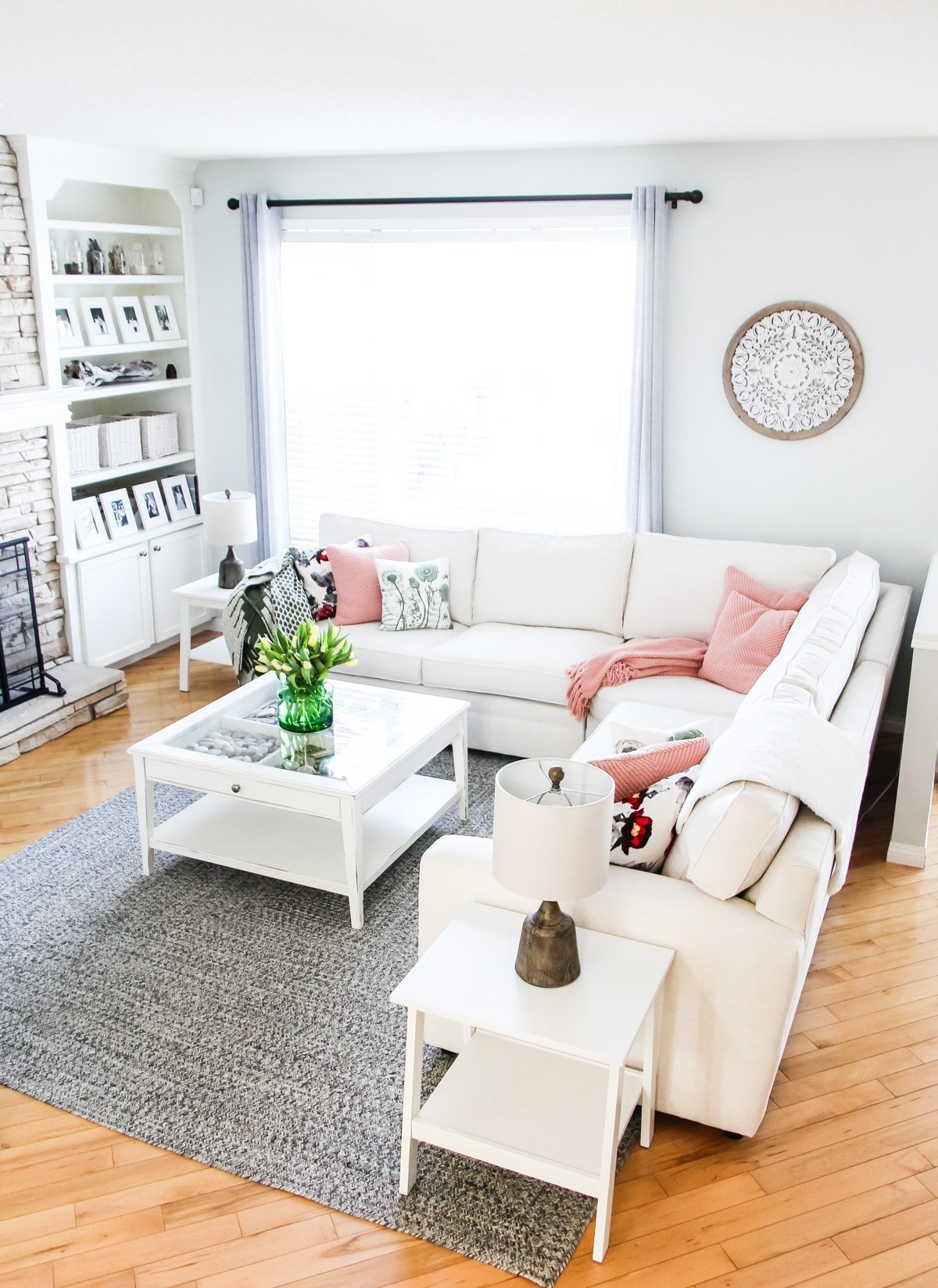 a picture of a white sectional couch in a living room. with throw pillows and blankets. on a coffee table is a bouquet of tulips