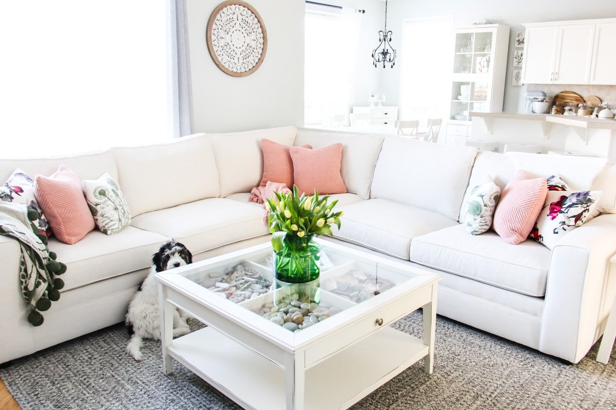 a white couch with pillows, a white coffee table with a green vase filled with tulips