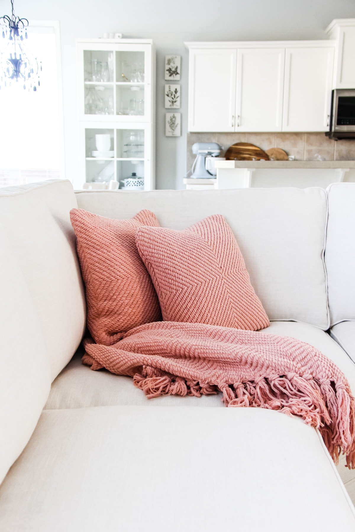 a picture of pink pillows and a pink blanket on a white couch