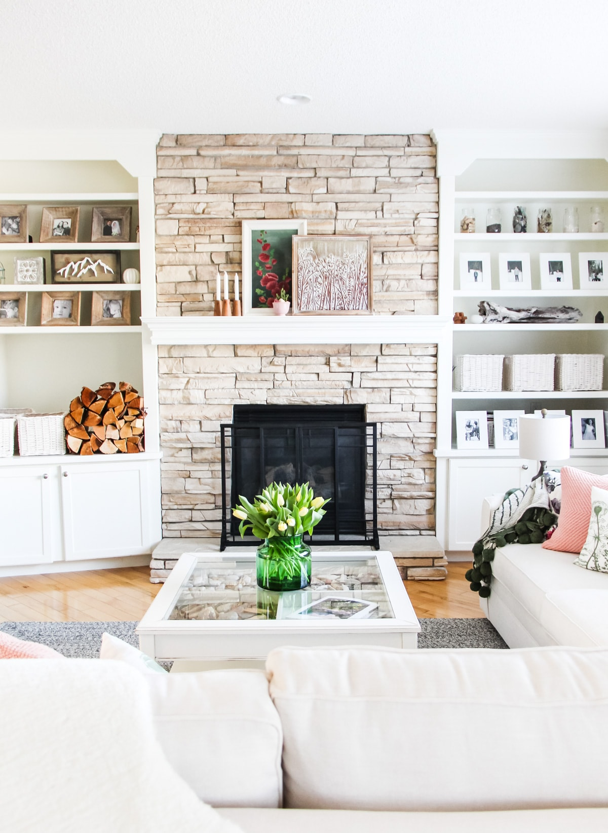 a stone mantel with white bookshelves on either side filled with picture frames, baskets, wood and art pieces