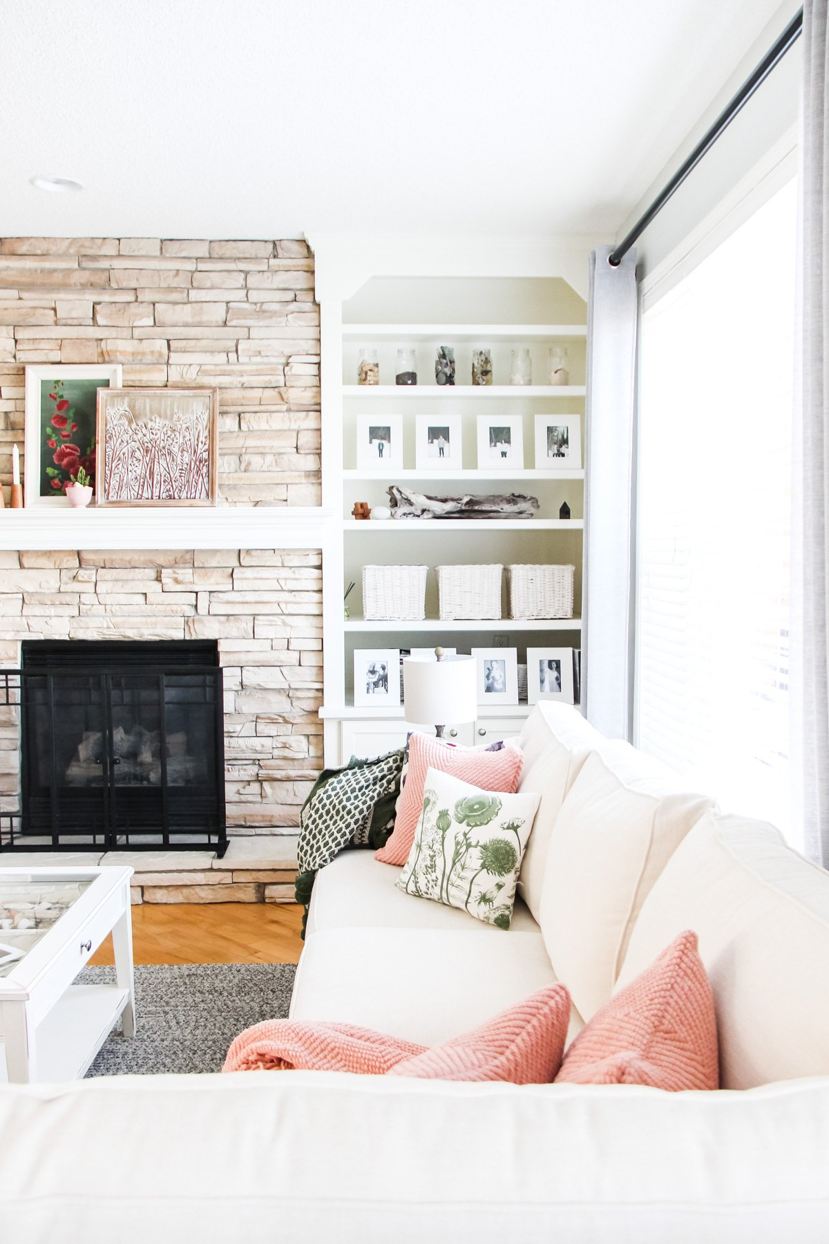 a stone fireplace with a white bookshelf to the right. in the forefront is a couch full of pillows and throw blankets