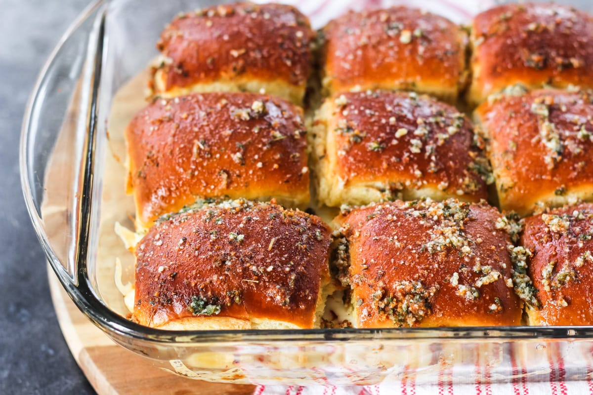 Pepperoni Pizza Sliders in a glass dish fresh out of the oven. topped with melted butter and oregano