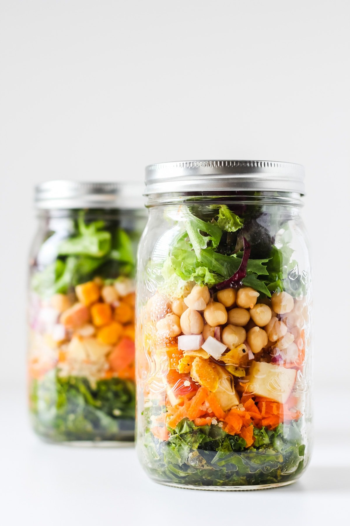 a close up of a Mason Jar Salad. in the background another jar of salad