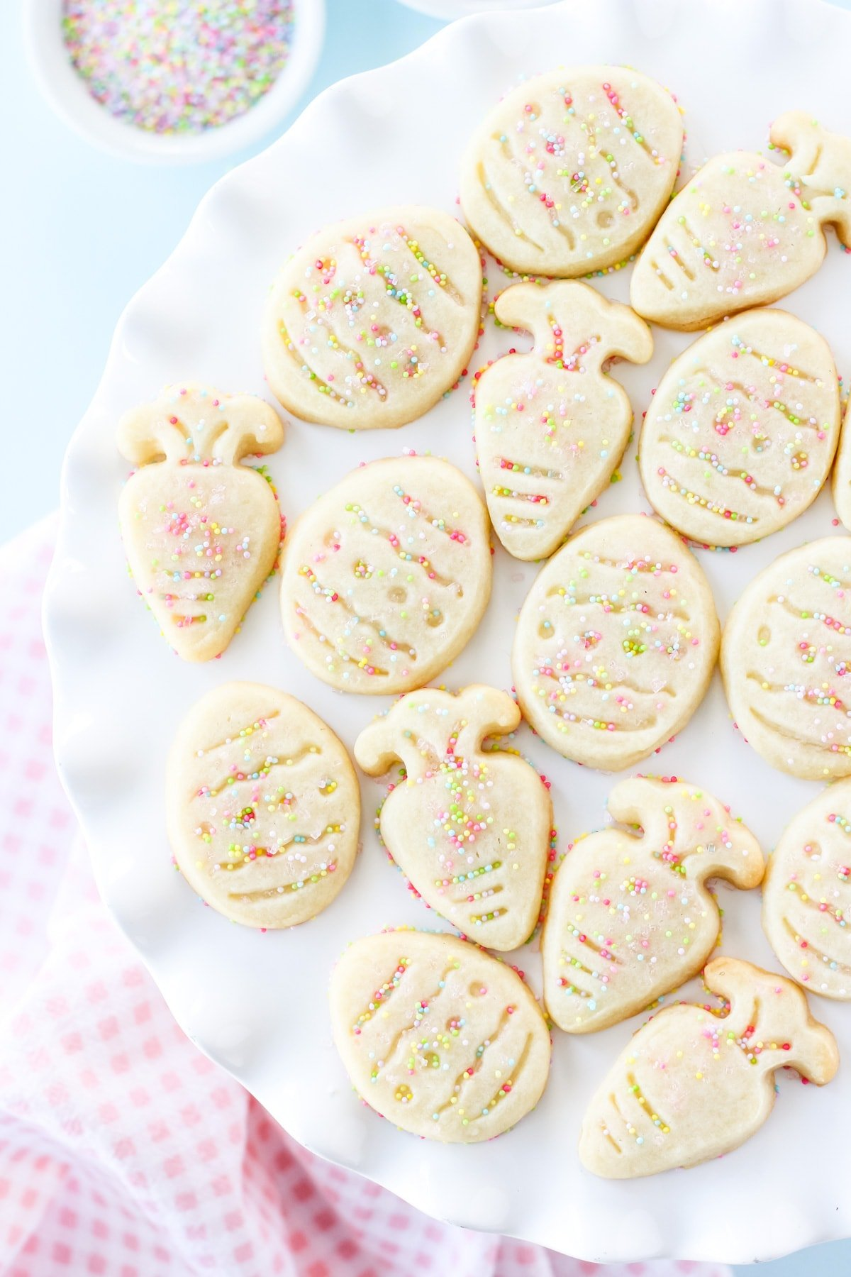 a white cake plate full of shortbread cut out cookies in the shapes of Easter eggs and carrots. in the background are small bowls of pastel colour sprinkles and a pink checked napkin
