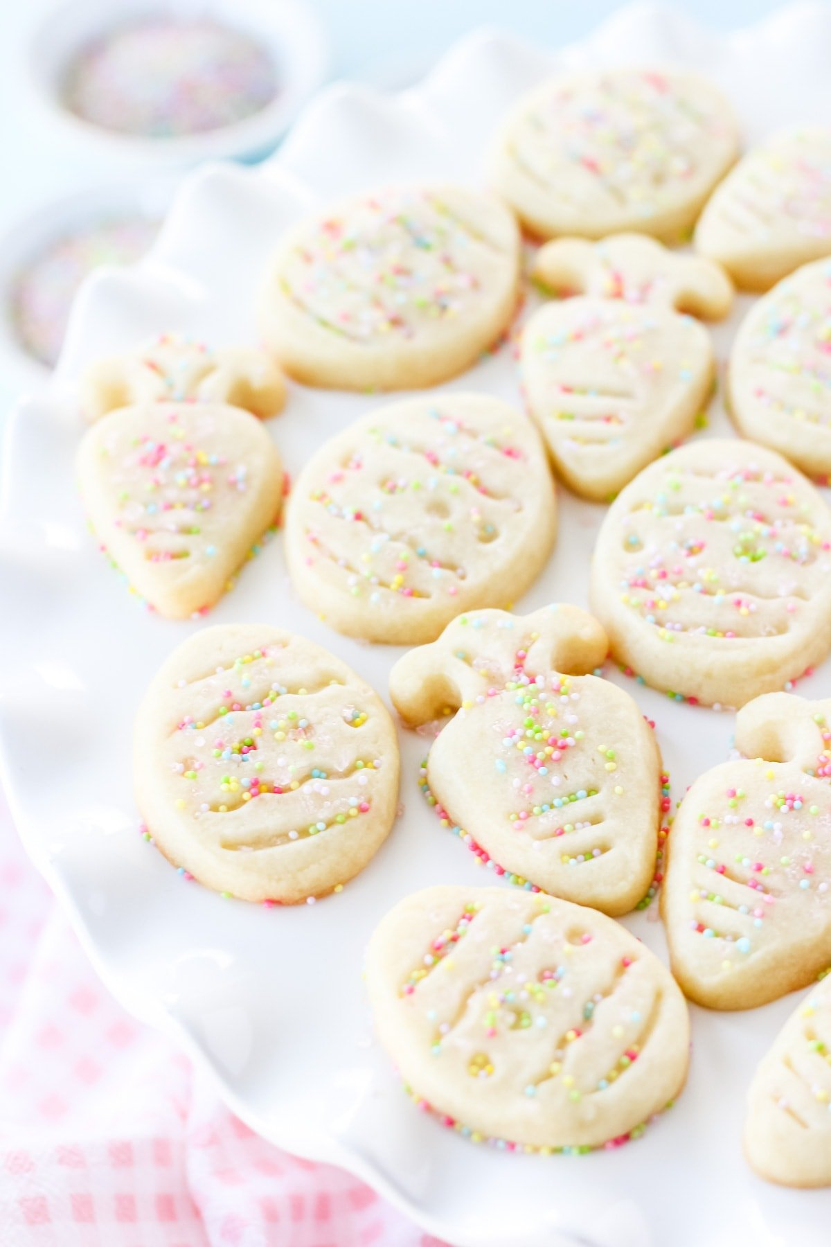 a close up image of a white cake plate full of shortbread cut out cookies in the shapes of Easter eggs and carrots. in the background are small bowls of pastel colour sprinkles and a pink checked napkin