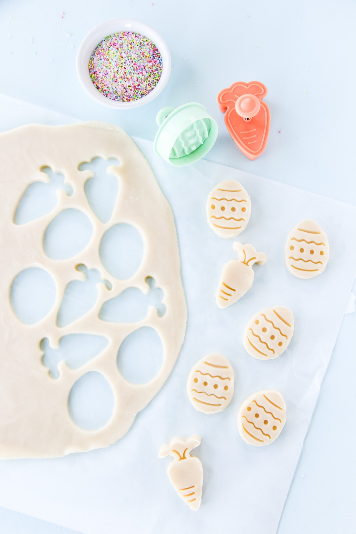 an image of shortbread cookie dough rolled out and cut out with cookie cutters. the shapes are carrots and Easter eggs. next to the cut out cookie dough are two cookie cutters and a bowl of pastel sprinkles