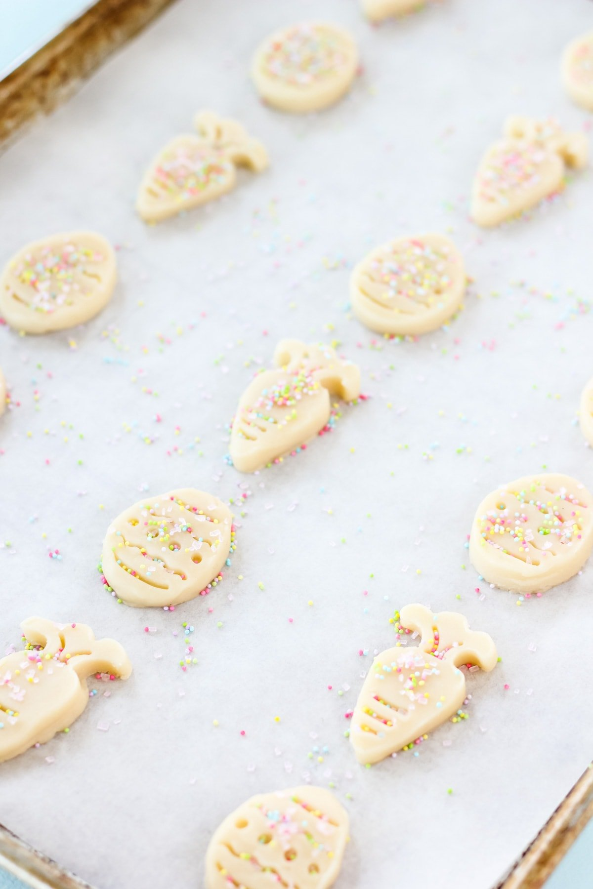 an image of a cookie sheet lined in parchment paper. on the sheet are raw cookie dough cut outs in the shapes of carrots and Easter eggs which are covered lightly in sprinkles