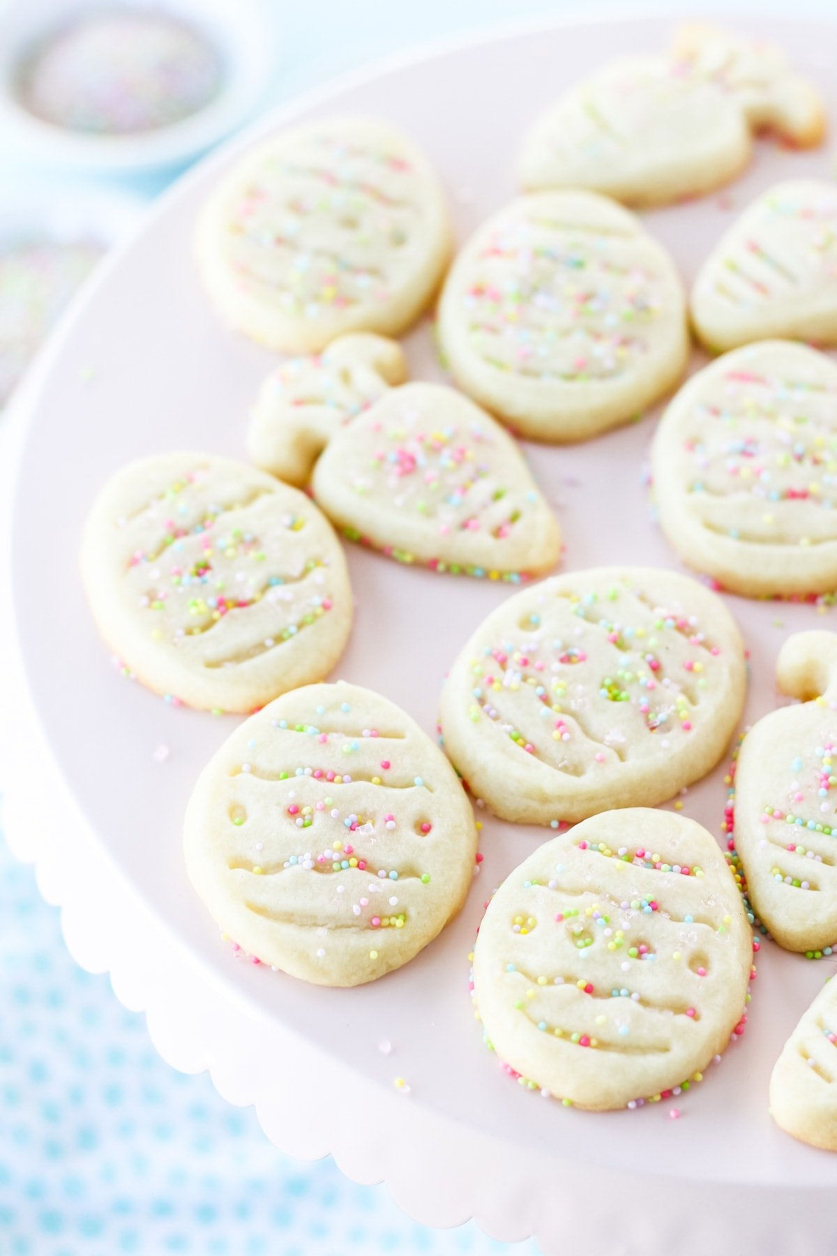 a pink cake plate full of shortbread cut out cookies in the shapes of Easter eggs and carrots. in the background is a small bowl of pastel colour sprinkles