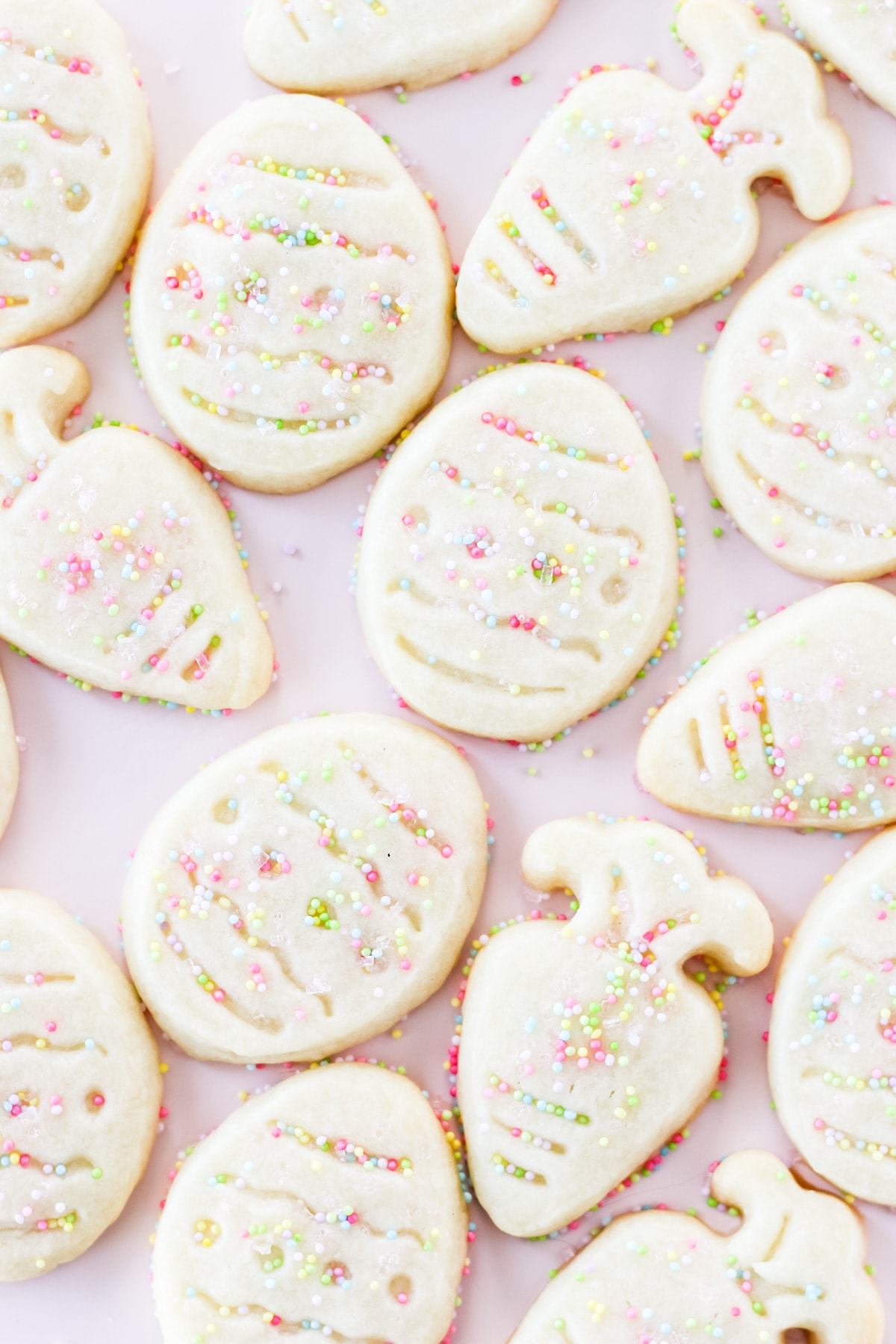 a pink cake plate full of shortbread cut out cookies in the shapes of Easter eggs and carrots