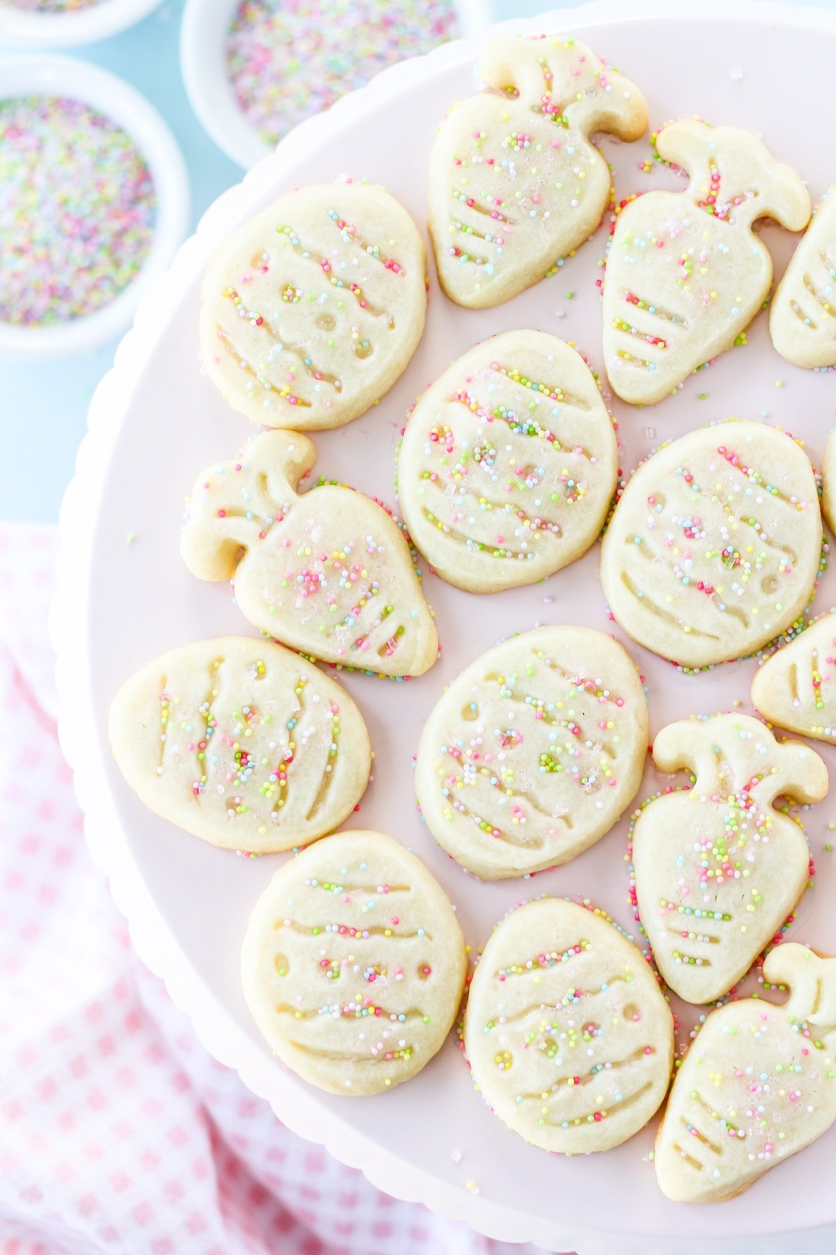 a pink cake plate full of shortbread cut out cookies in the shapes of Easter eggs and carrots. in the background are small bowls of pastel colour sprinkles and a pink checked napkin