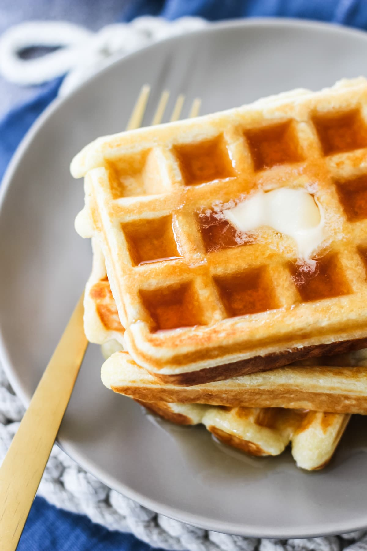 a top down view of a stack of sour cream waffles. the top waffle is has melted butter and syrup. in the background is a grey plate, gold fork, beige hot pad and blue linen napkin