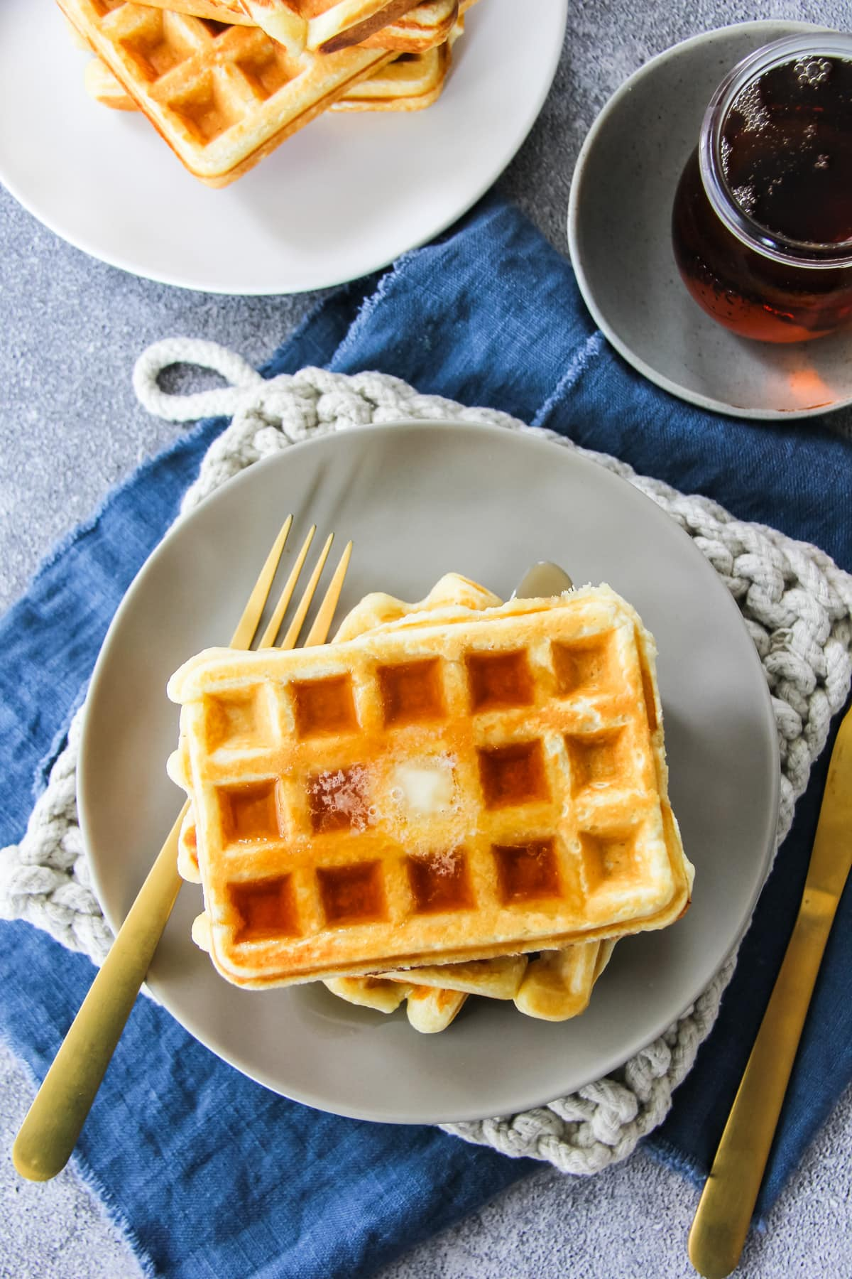 a top down view of a stack of sour cream waffles. the top waffle is has melted butter and syrup. in the background is a white plate with more waffles, a jar of syrup, gold fork, beige hot pad and blue linen napkin