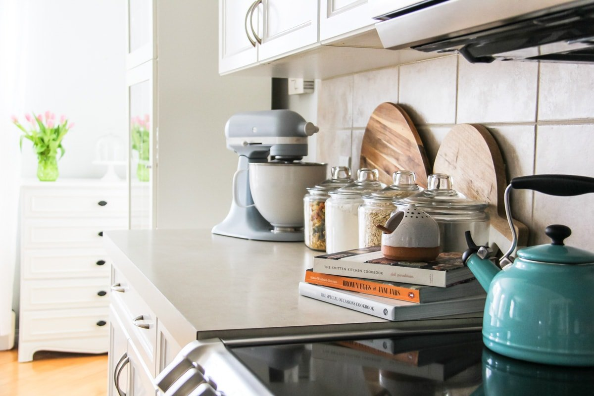 a kitchen counter with a light blue kitchenaid mixer, teal kettle, cookbooks and jars of dried goods