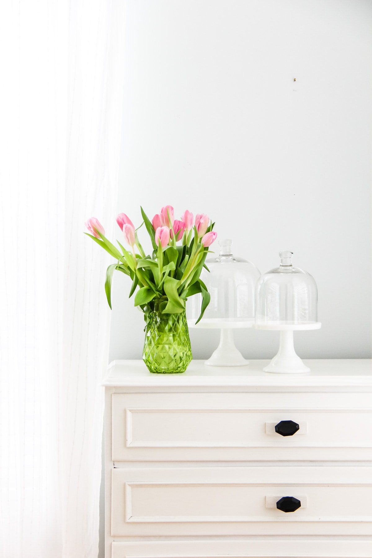 a bouquet of pink tulips in a green glass vase, sitting on a white chest of drawers