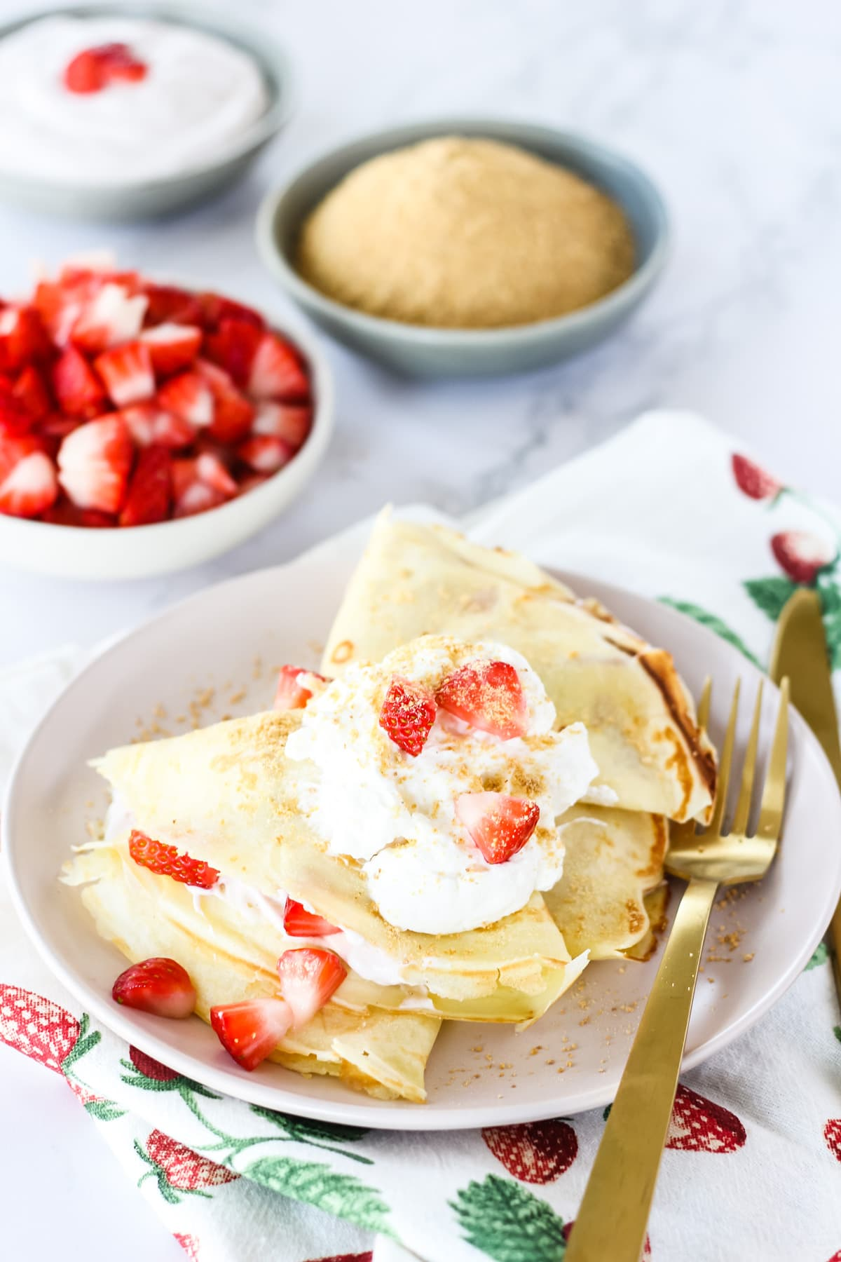 a top down view of a plate of two Strawberry Cheesecake Crepes garnished with whipping cream, chopped strawberries and graham cracker crumbs. in the background are small bowls of chopped strawberries, graham cracker crumbs, whipping cream and a strawberry linen napkin
