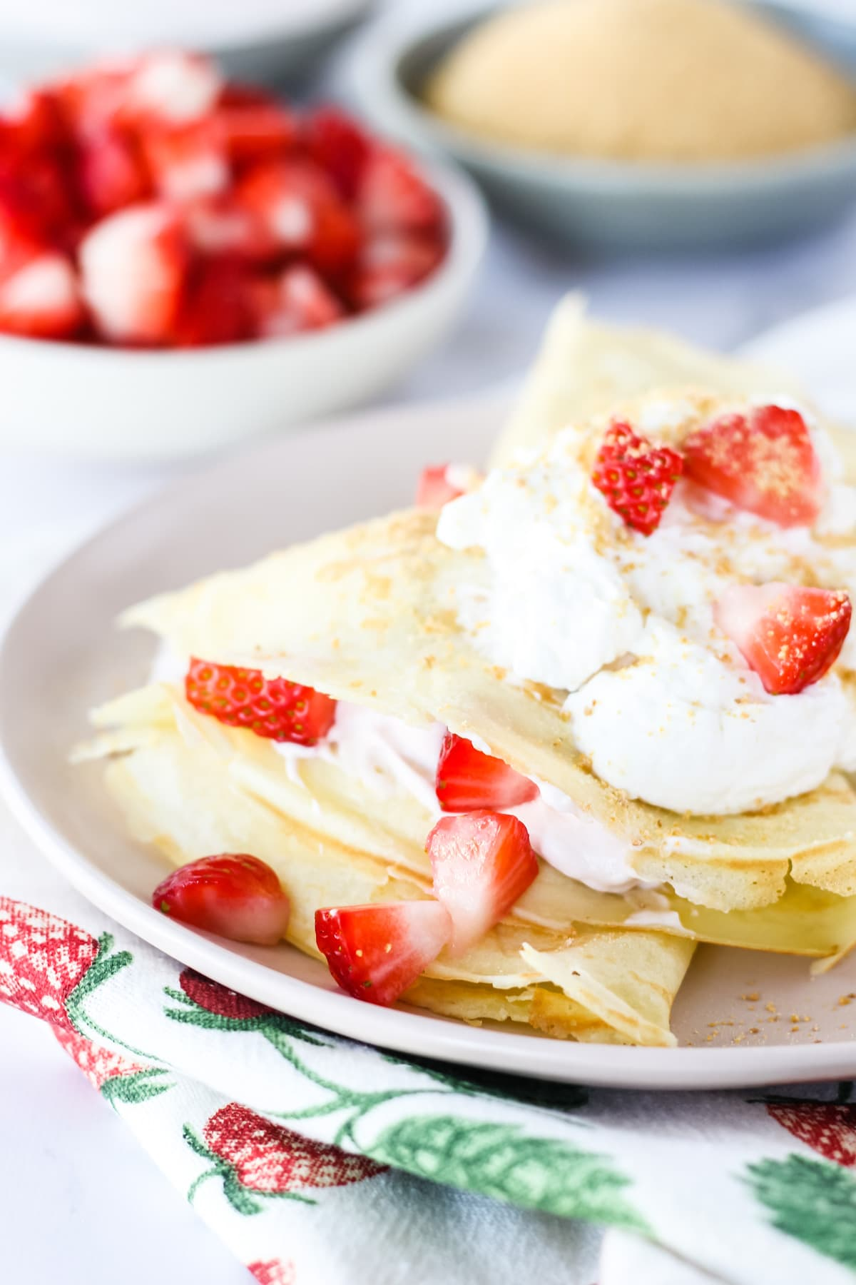 a close up side view of a plate of Strawberry Cheesecake Crepes garnished with whipping cream, chopped strawberries and graham cracker crumbs. in the background are small bowls of chopped strawberries, graham cracker crumbs, whipping cream and a strawberry linen napkin