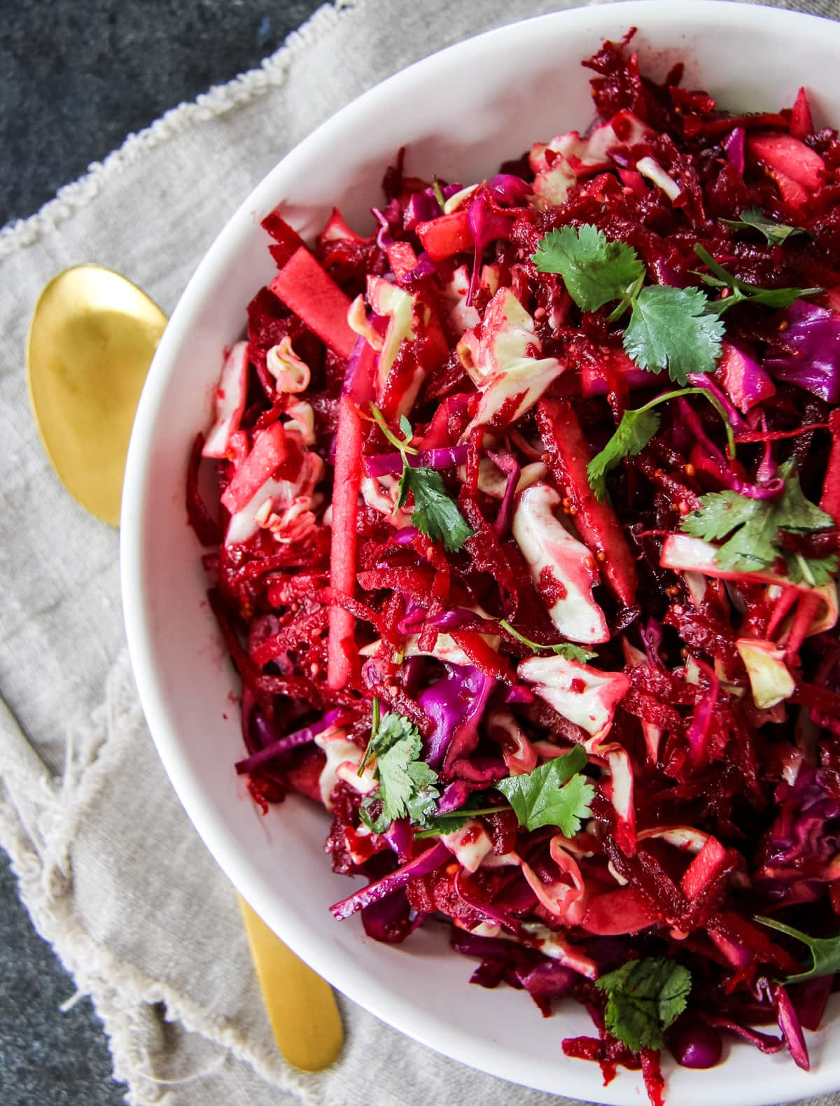 a top down view of a bowl full of apple beet slaw. the bowl is sitting on a brown linen napkin and dark background. next to the bowl is a gold spoon