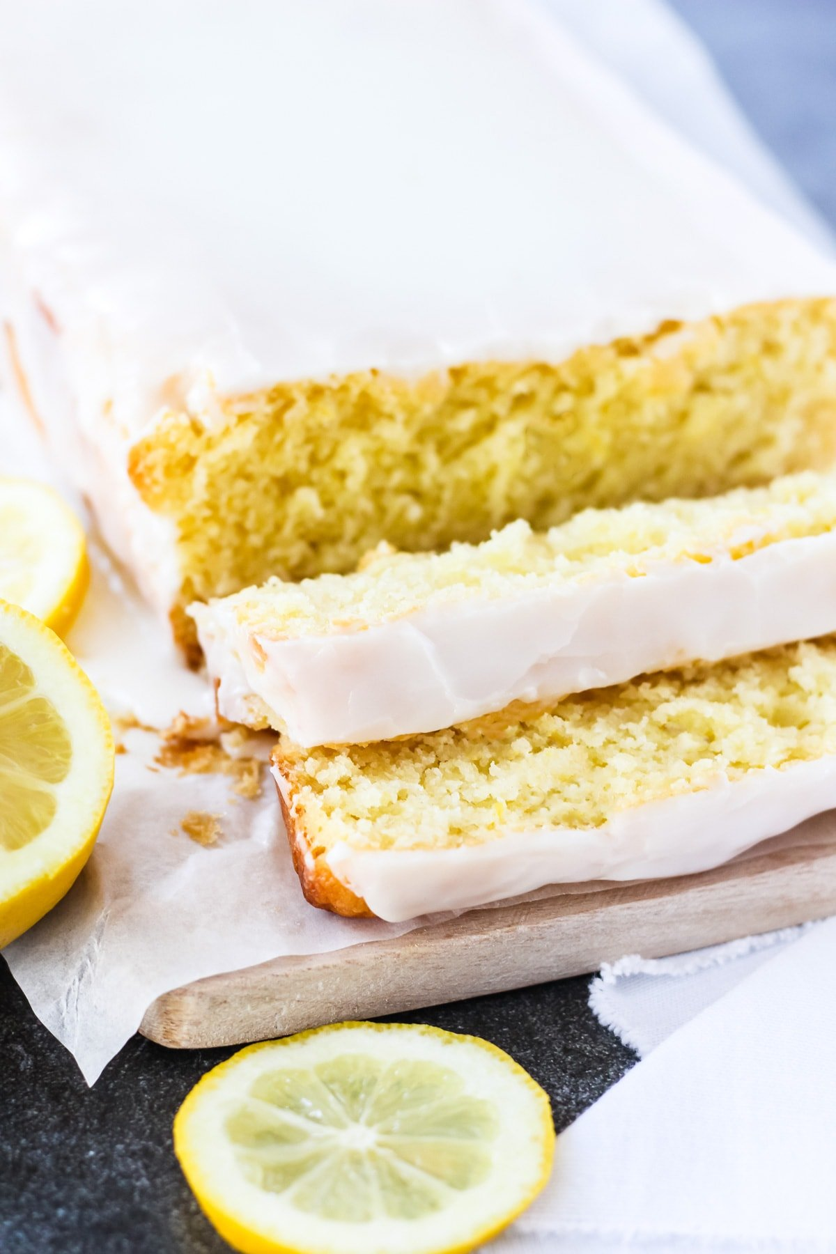 a side view of a lemon loaf cut into slices. it's topped with white icing. on the side are slices of fresh lemon
