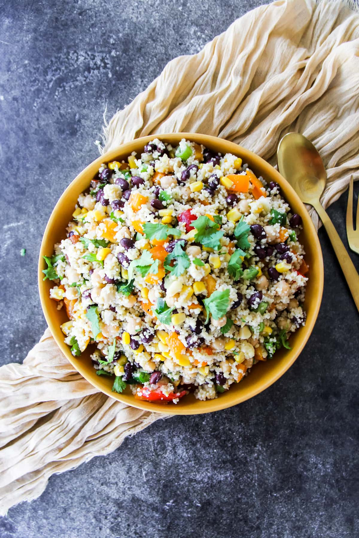 a top down view of a colourful Tex Mex Couscous Salad in a mustard yellow bowl. the bowl is sitting on a soft cream napkin and dark background. to the right is a gold spoon