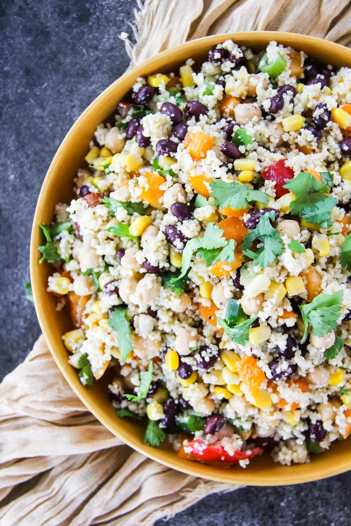a top down view of a colourful Tex Mex Couscous Salad in a mustard yellow bowl. the bowl is sitting on a soft cream napkin and dark background.
