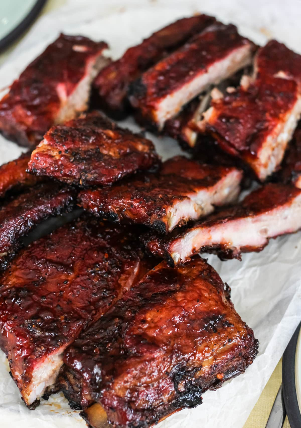 a parchment paper lined tray filled with cut saucy barbecued ribs cut into pieces