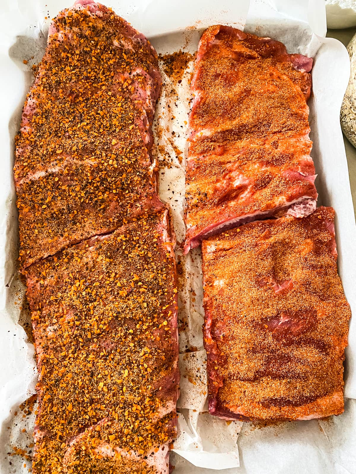 a parchment paper lined tray with two racks for raw ribs covered in a brown sugar spice rub.