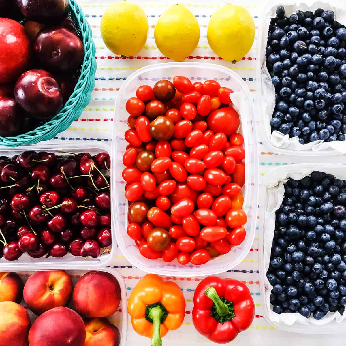 a top down view of a tea towel covered with lemons, peppers, blueberries, cherries, grape tomatoes, plums and nectarines