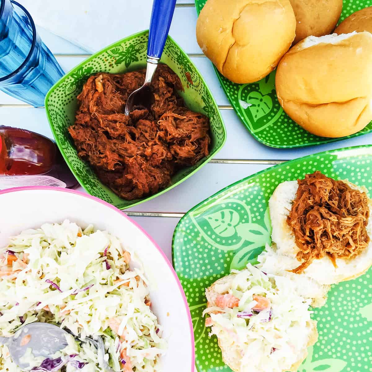 a top down view of an outdoor dinner table with a pulled pork dinner. there is a bowl of pulled pork, a bowl of coleslaw, a plate of buns