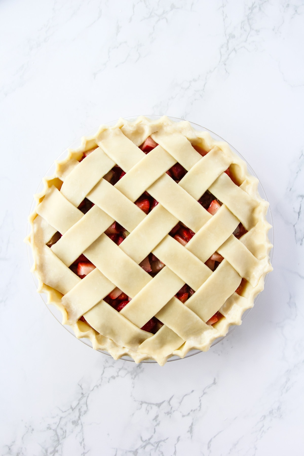 a top down view of an unbaked pie with a lattice crust. it is sitting on a marble background