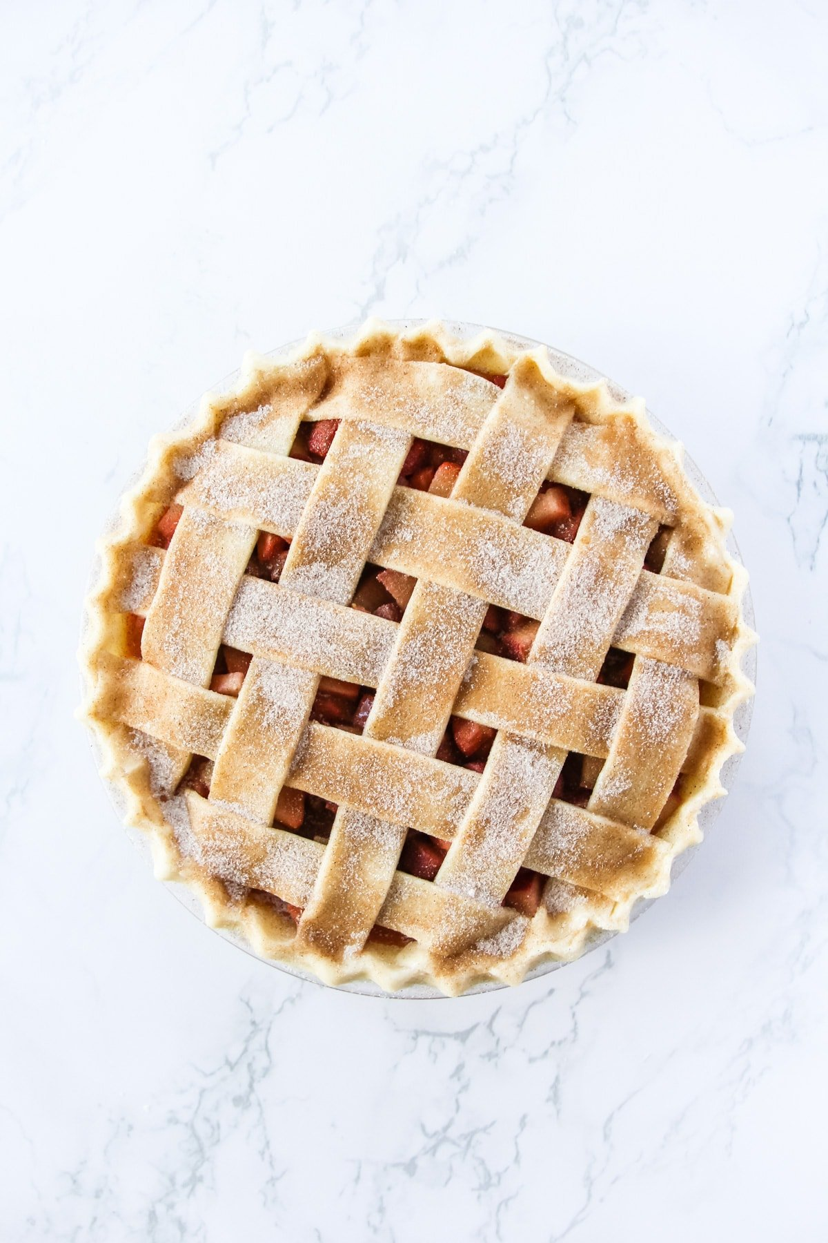 a top down view of an unbaked pie with a lattice crust. the crust is sprinkled with cinnamon and sugar. the background is a marble table top
