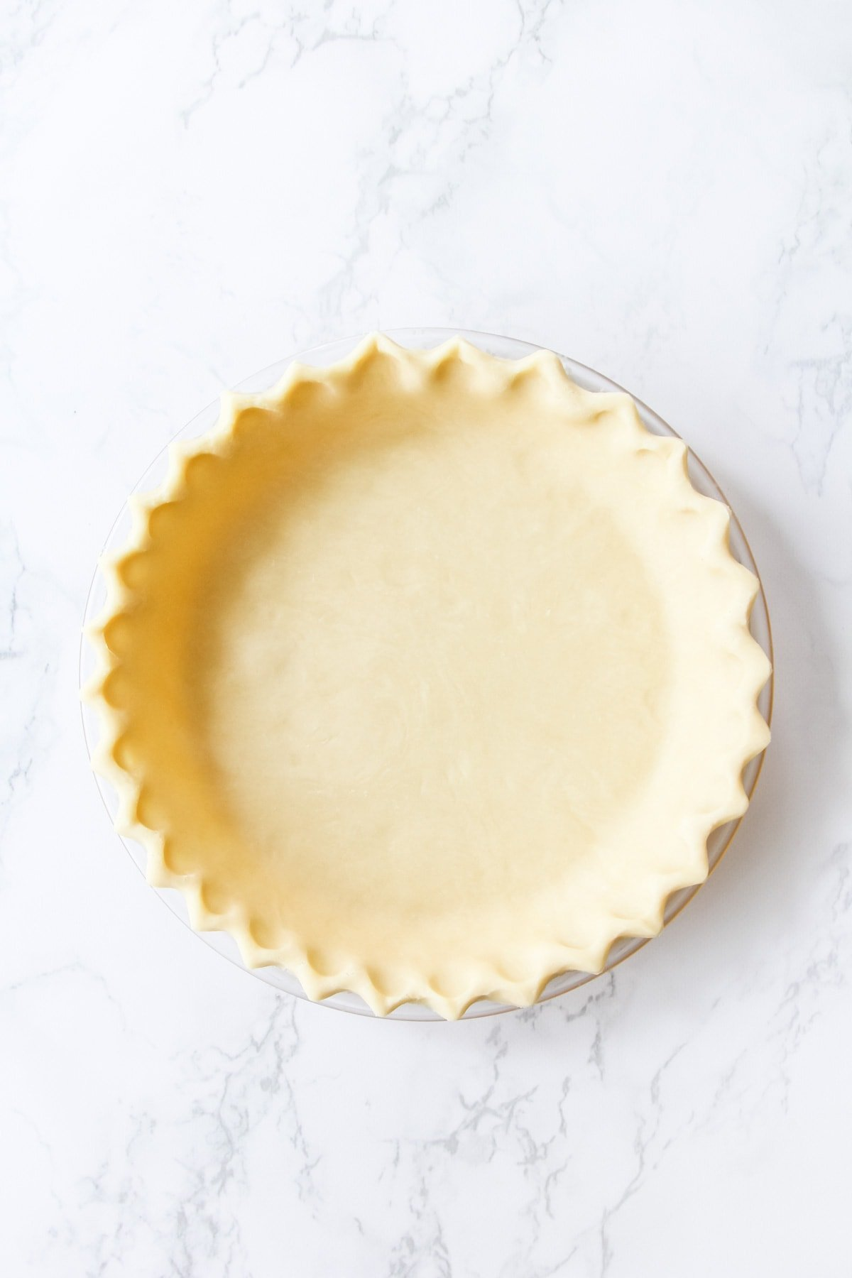 a top down view of an unbaked Crimped Pie Crust on a marble background