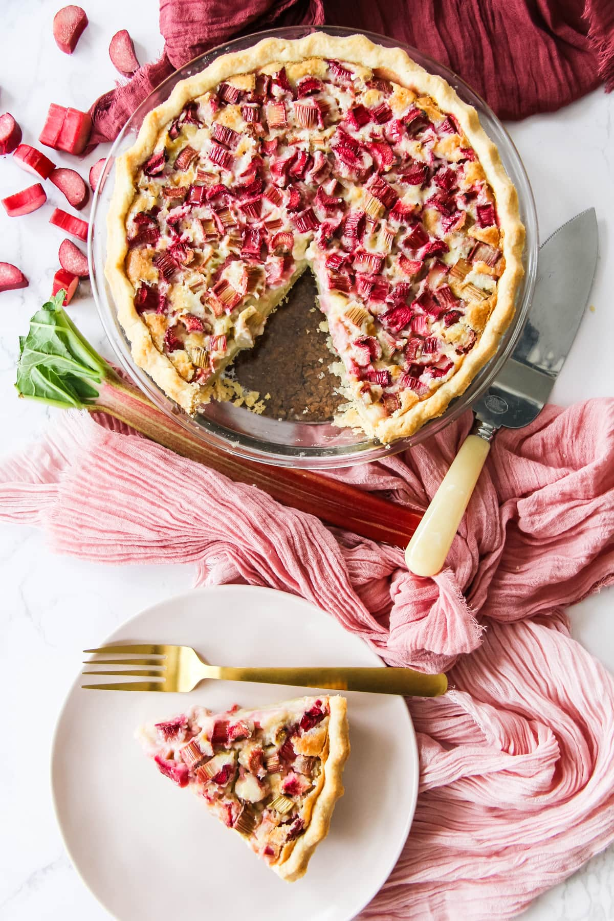 a top down view of a baked rhubarb custard pie with a slice cut out of it, as well as a soft pink plate with the slice of pie and a gold fork. in the background are pink and wine coloured napkins, a rhubarb stock, pieces of chopped rhubarb and a pie server