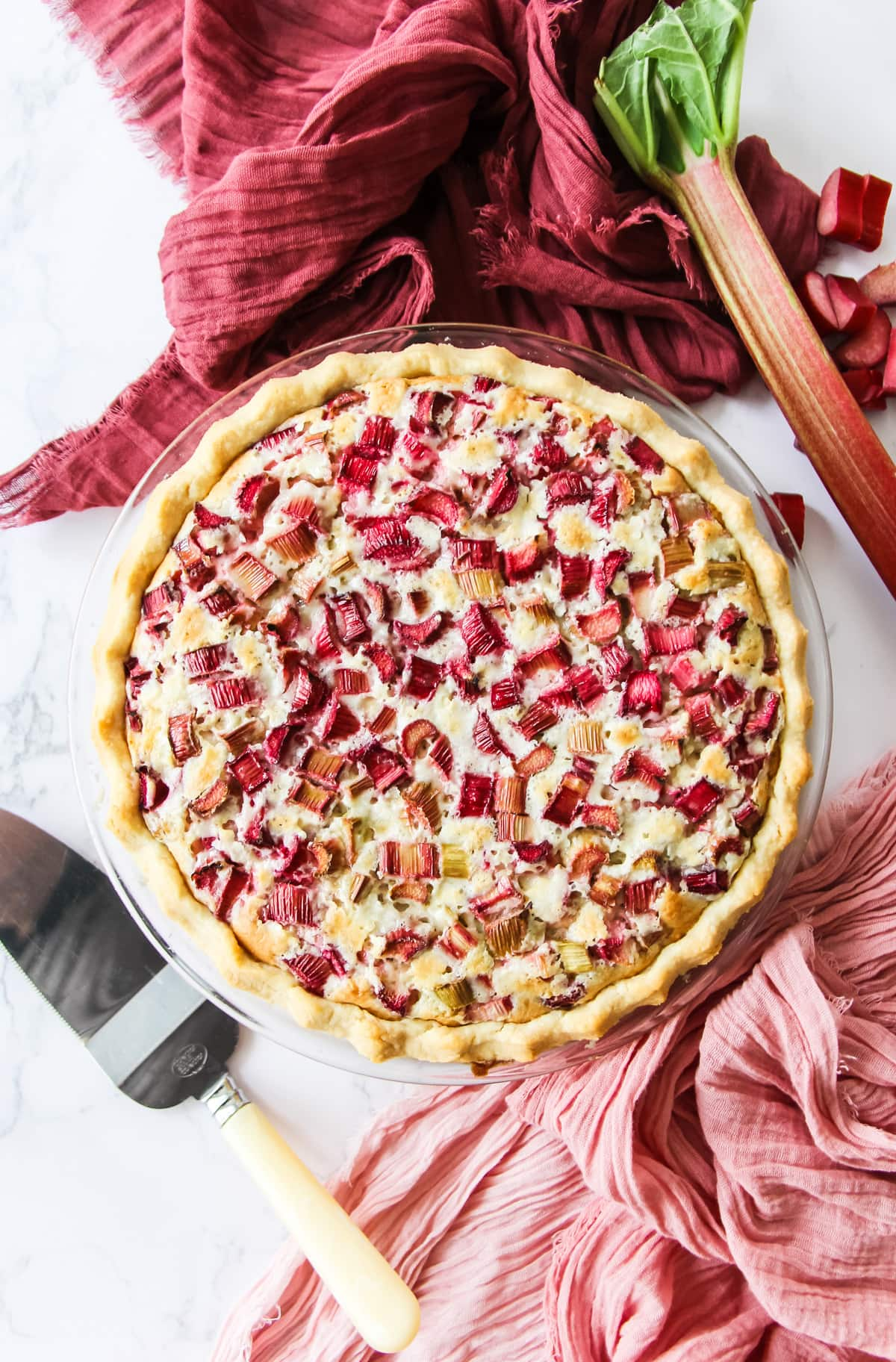 a top down view of a baked rhubarb custard pie. in the background are pink and wine coloured napkins, a rhubarb stock, pieces of chopped rhubarb and a pie server