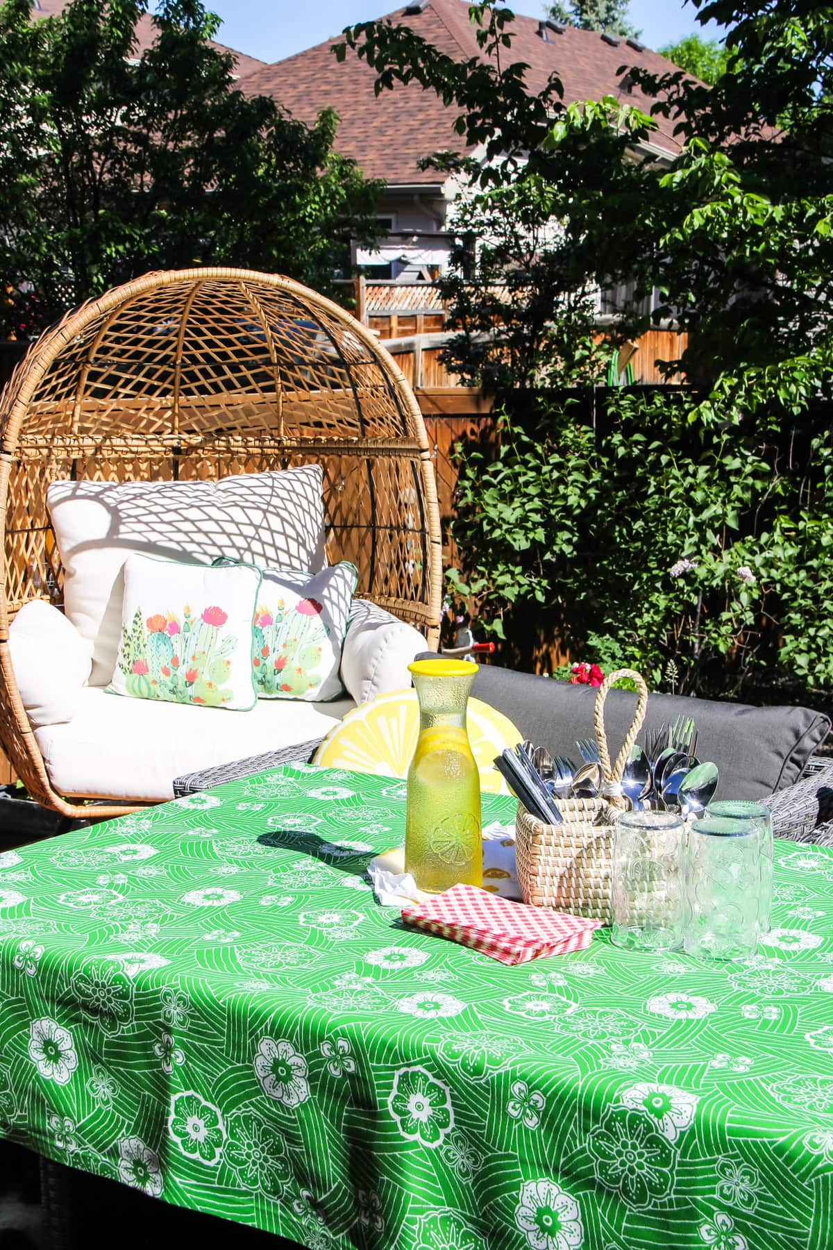 a table with a green and white flowered tablecloth, a jug of lemonade, red and white napkins, glasses and a container of cutlery. in the background is a wicker egg chair with pillows