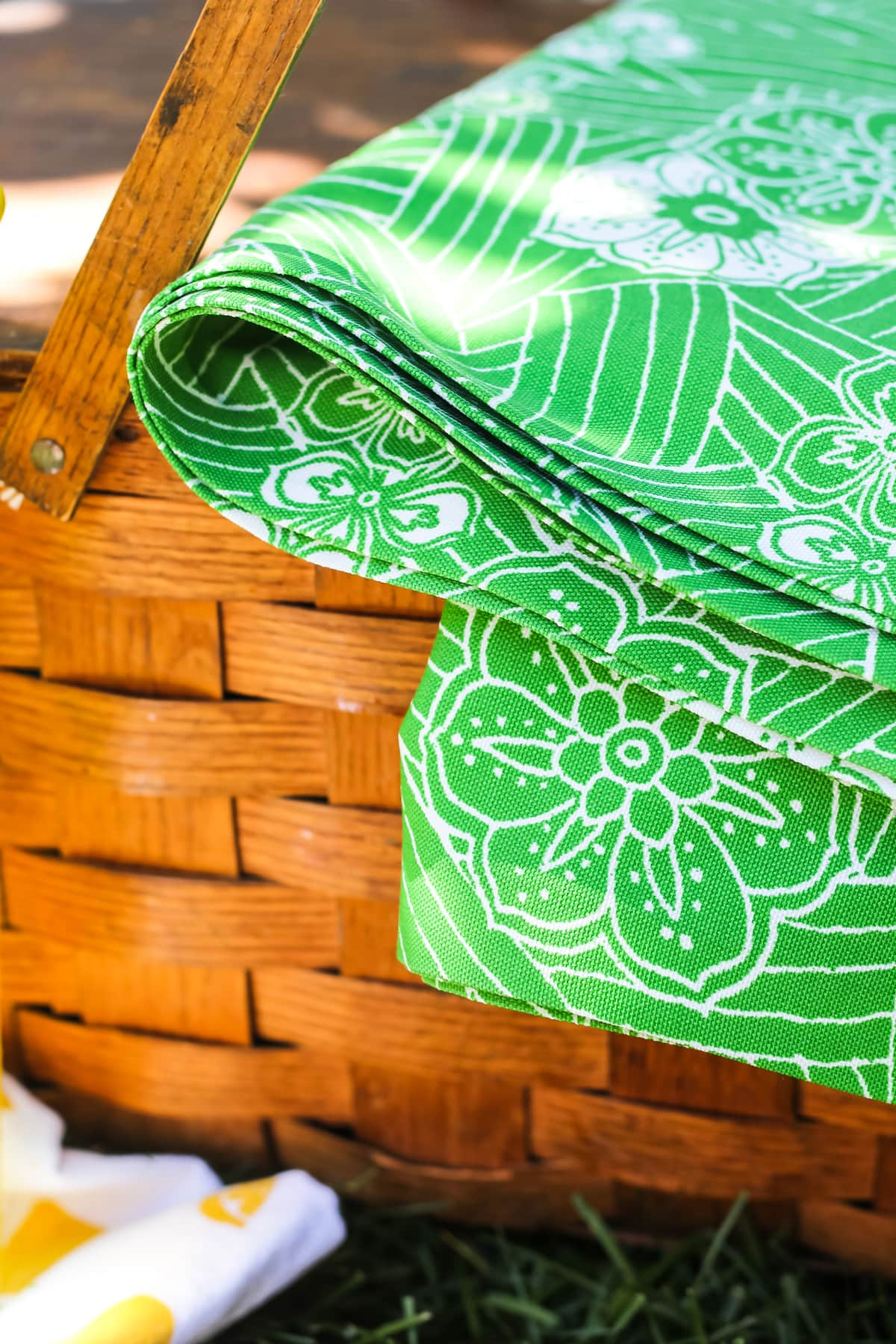 a brown wood picnic basket sitting on green grass with a green and white picnic blanket draped over one side of it.