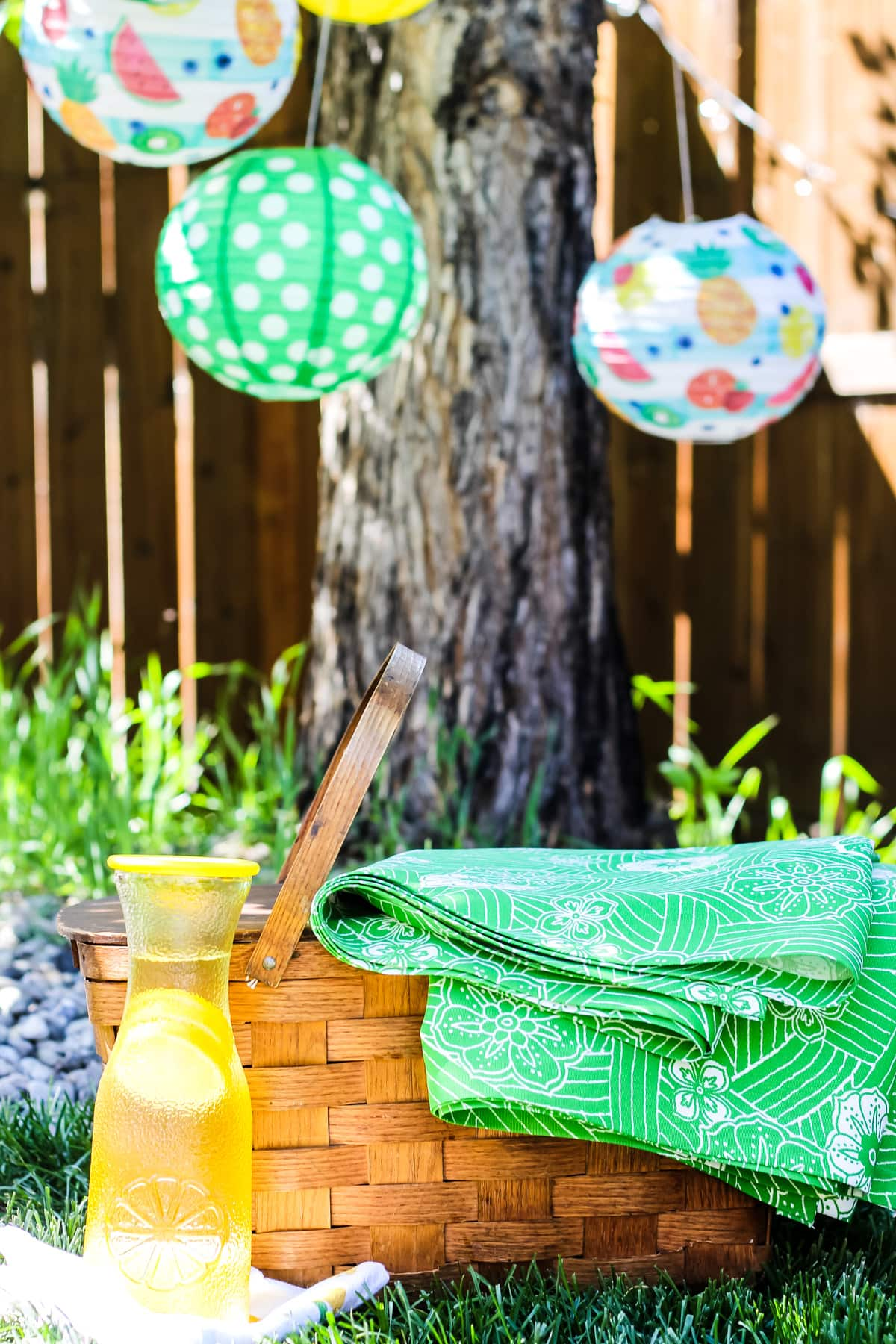 a brown wood picnic basket sitting on green grass. a green and white picnic blanket is draped over one side of it. in front is a jug of lemonade. in the background are paper lanterns hanging from a tree
