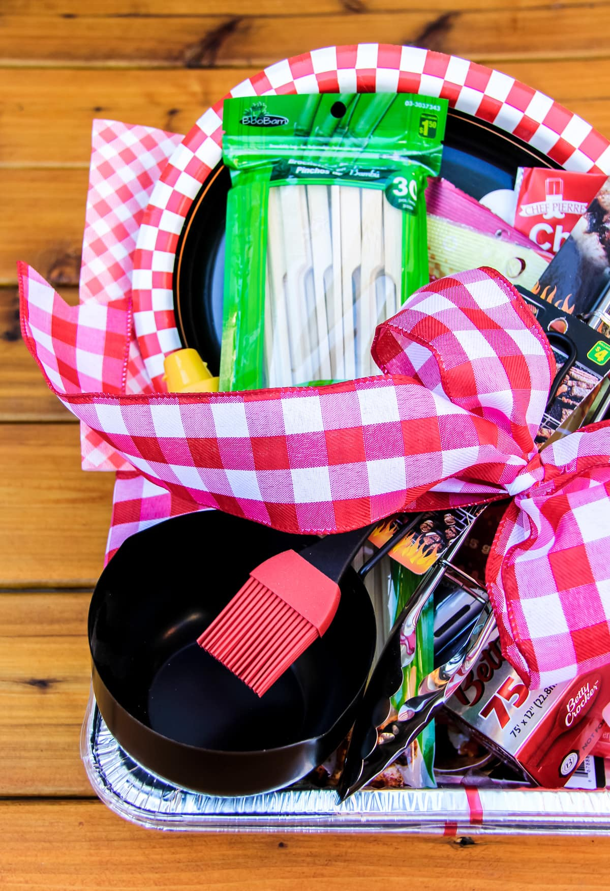 a top down view of half of a father's day gift of barbecue items like a basting brush and bowl, skewers, tongs and a red gingham ribbon