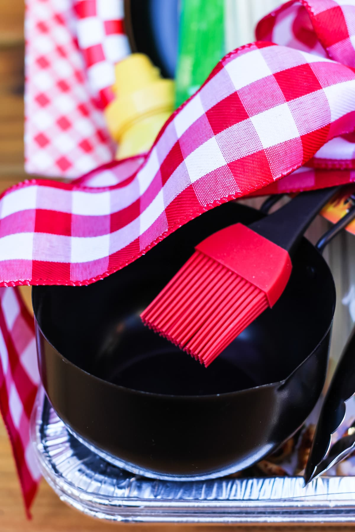 a basting brush and a black bowl tied with a red gingham ribbon