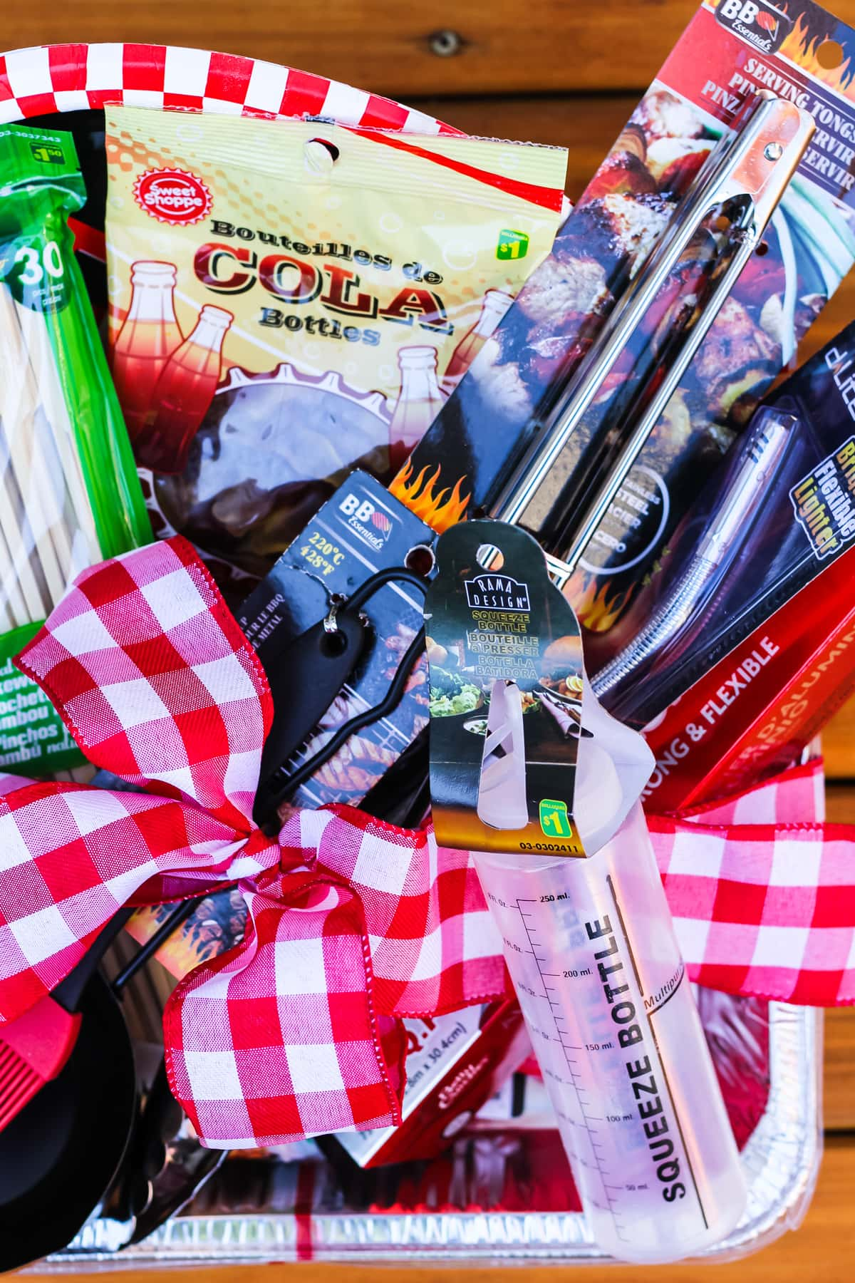 a top down view of a father's day gift basket of barbecue items: a basting brush and bowl, skewers, tongs, barbecue lighter, candy, squirt bottle and a red gingham ribbon