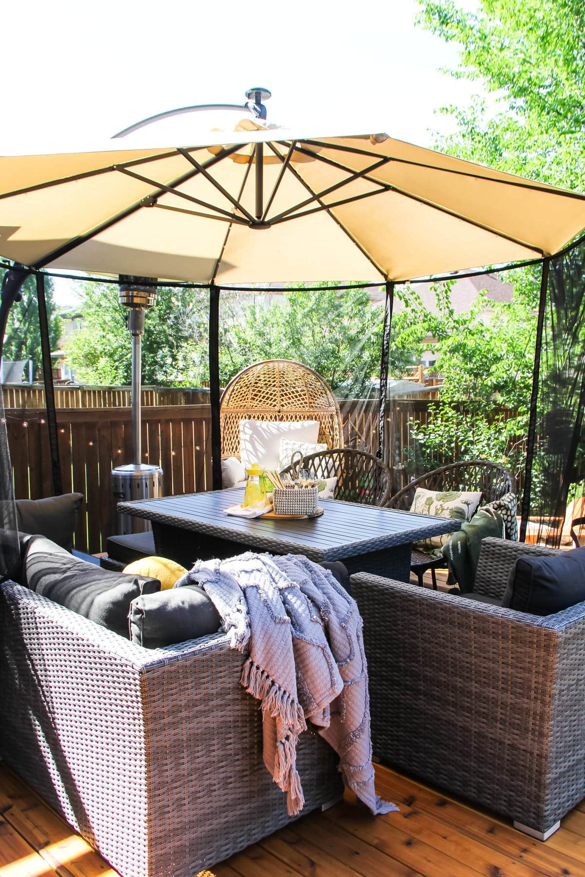 a table and chairs sits under a patio umbrella