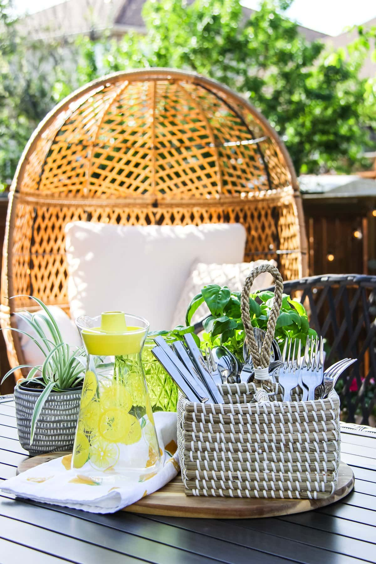 a basket of cutlery, a yellow glass jug and a plant sit on a table. in the background is a wicker chair